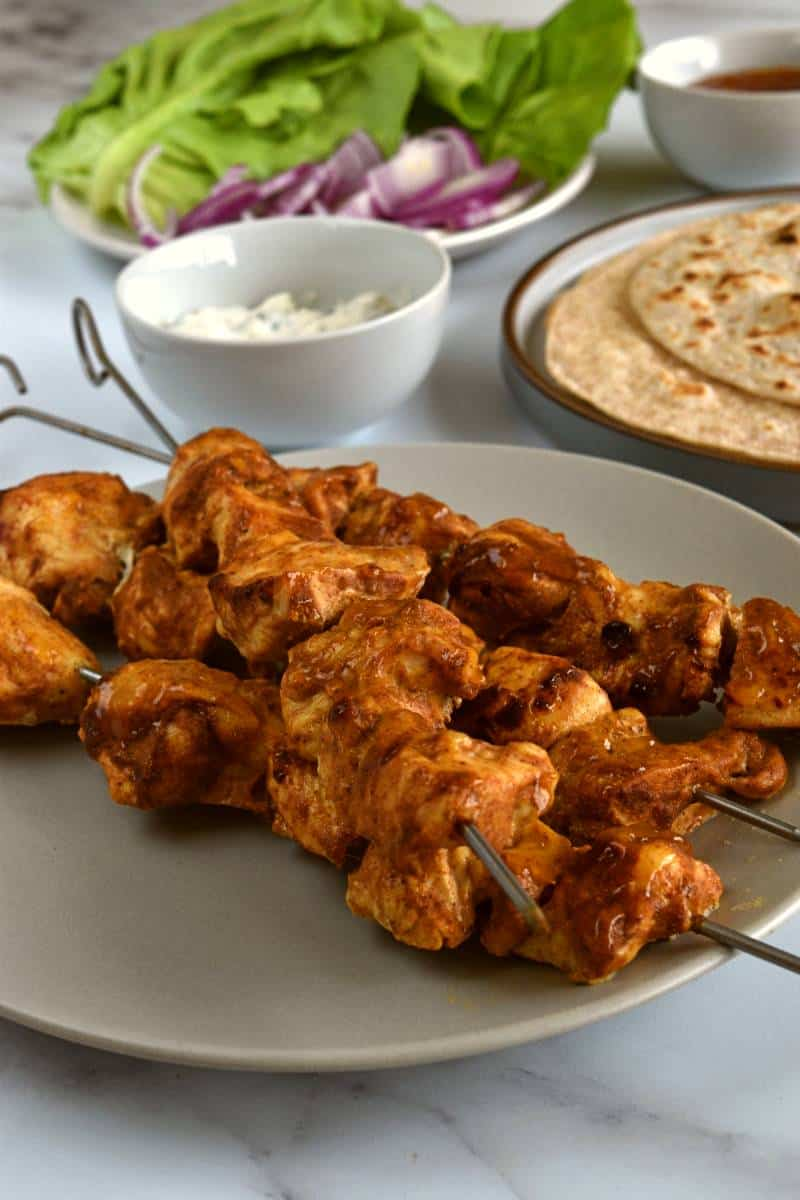 Chicken tikka kebab with lettuce and wraps in the background.