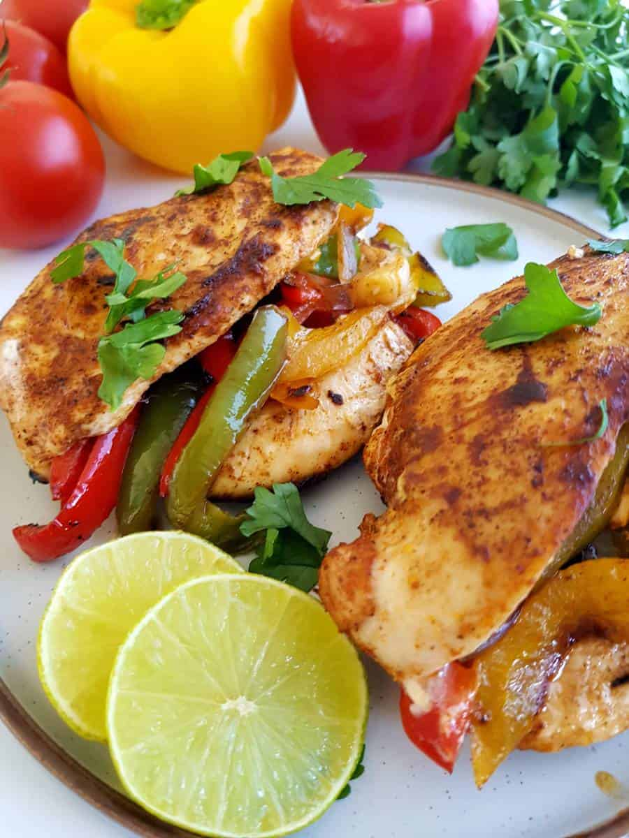 Fajita stuffed chicken on a plate with lime slices.