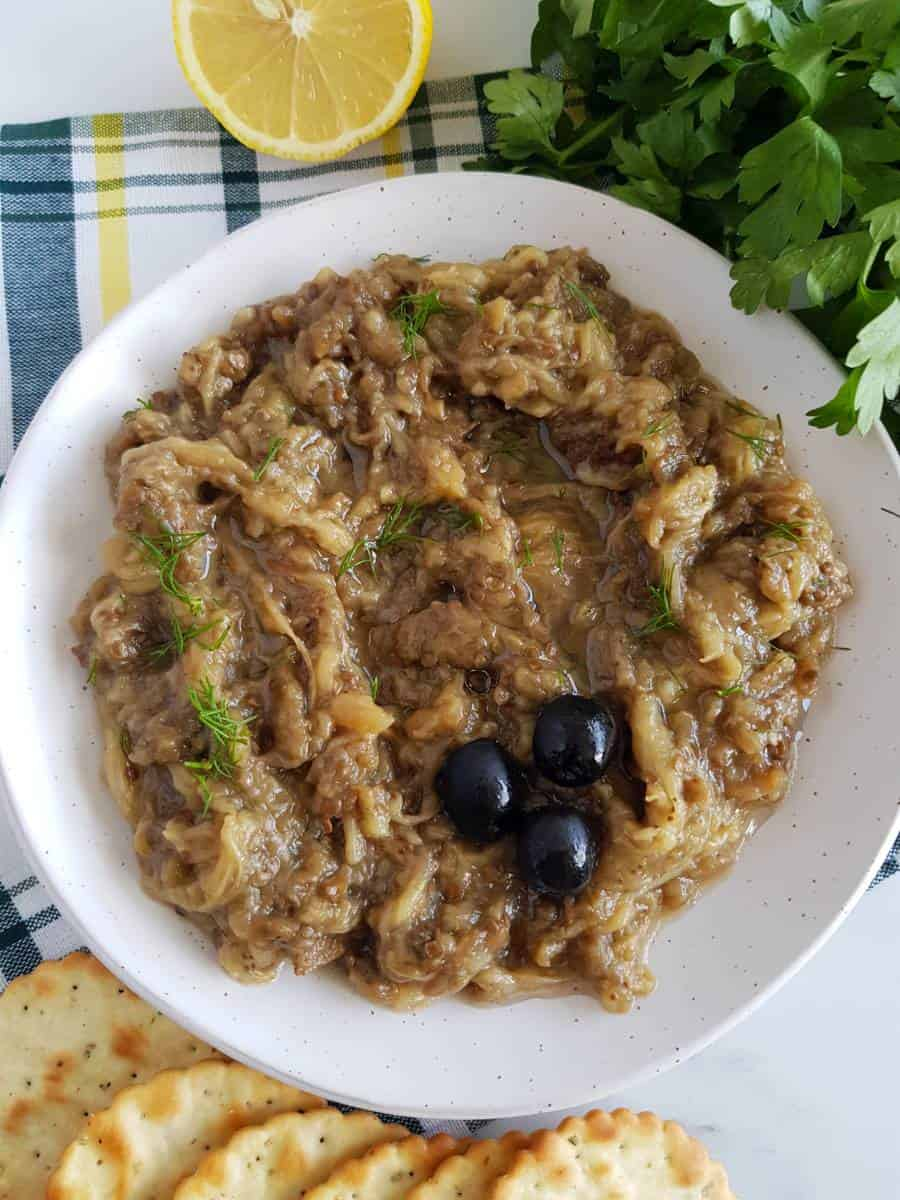 Greek eggplant dip in a bowl with parsley, lemon and crackers on the side.