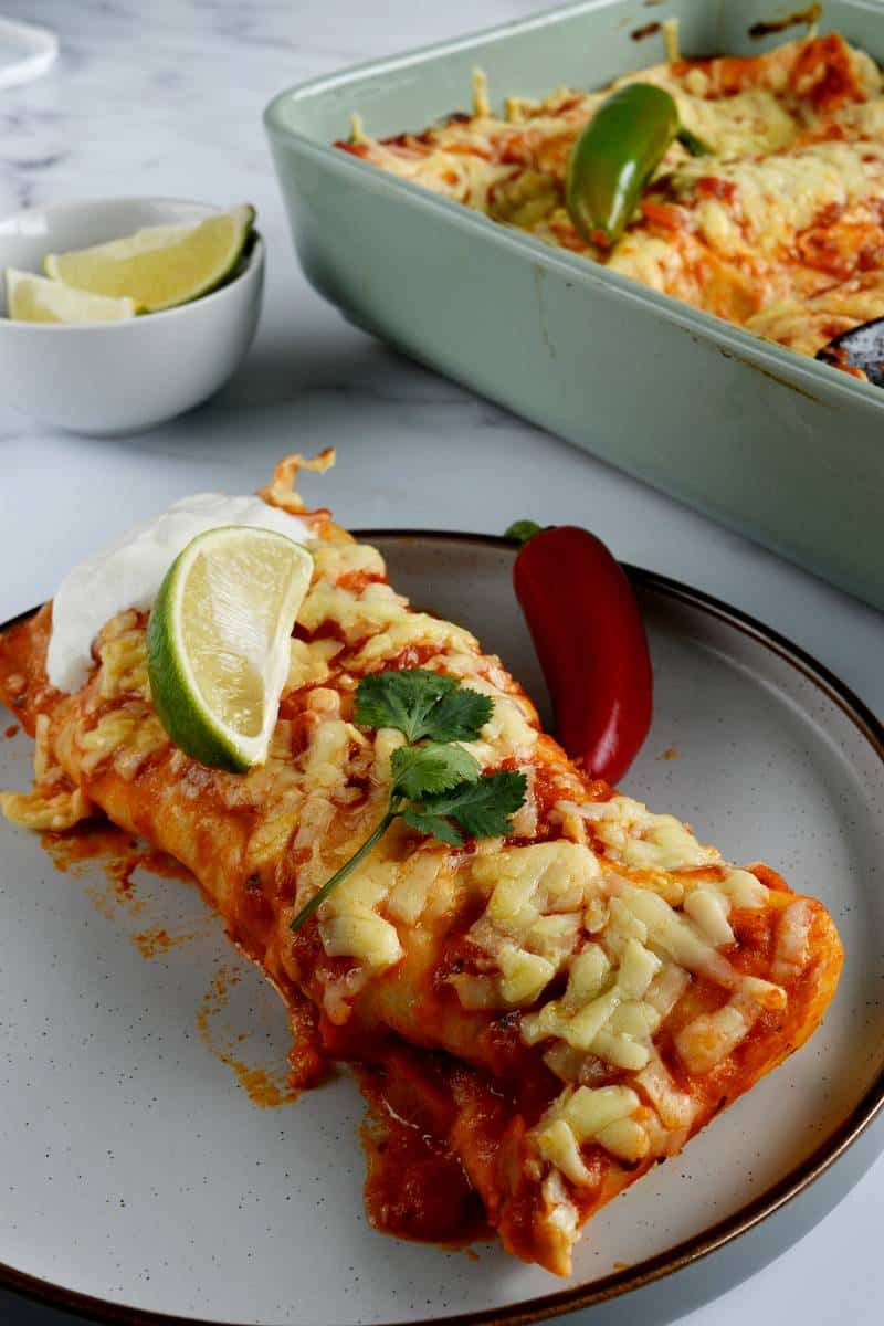 Ground turkey enchiladas on a plate, topped with lime and cilantro.