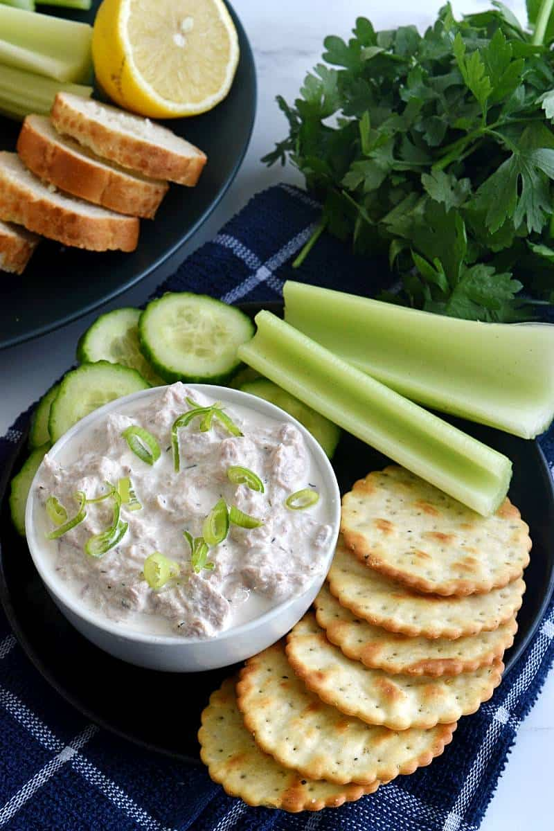 Healthy tuna dip with crackers and celery sticks.