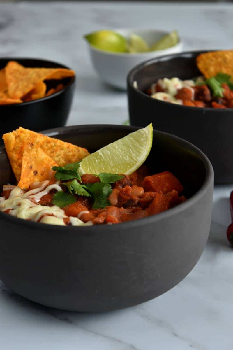 Mixed bean chilli in bowls, topped with lime wedge, tortilla chips and cheese.