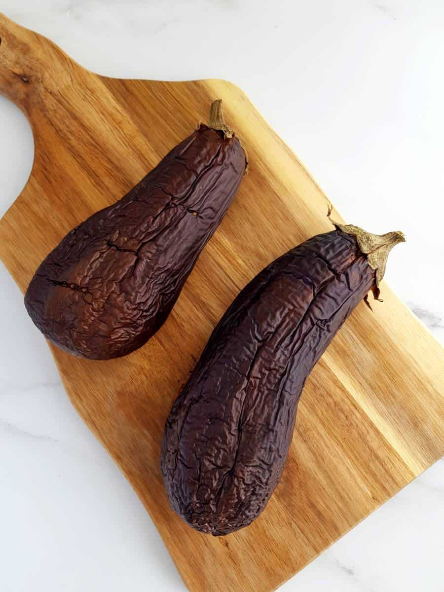 Roasted eggplants on a wooden board.