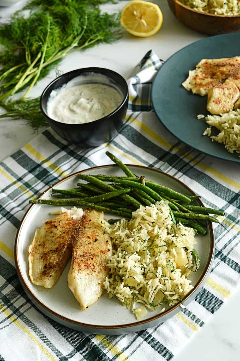 Tilapia with rice and green beans at a dinner table.