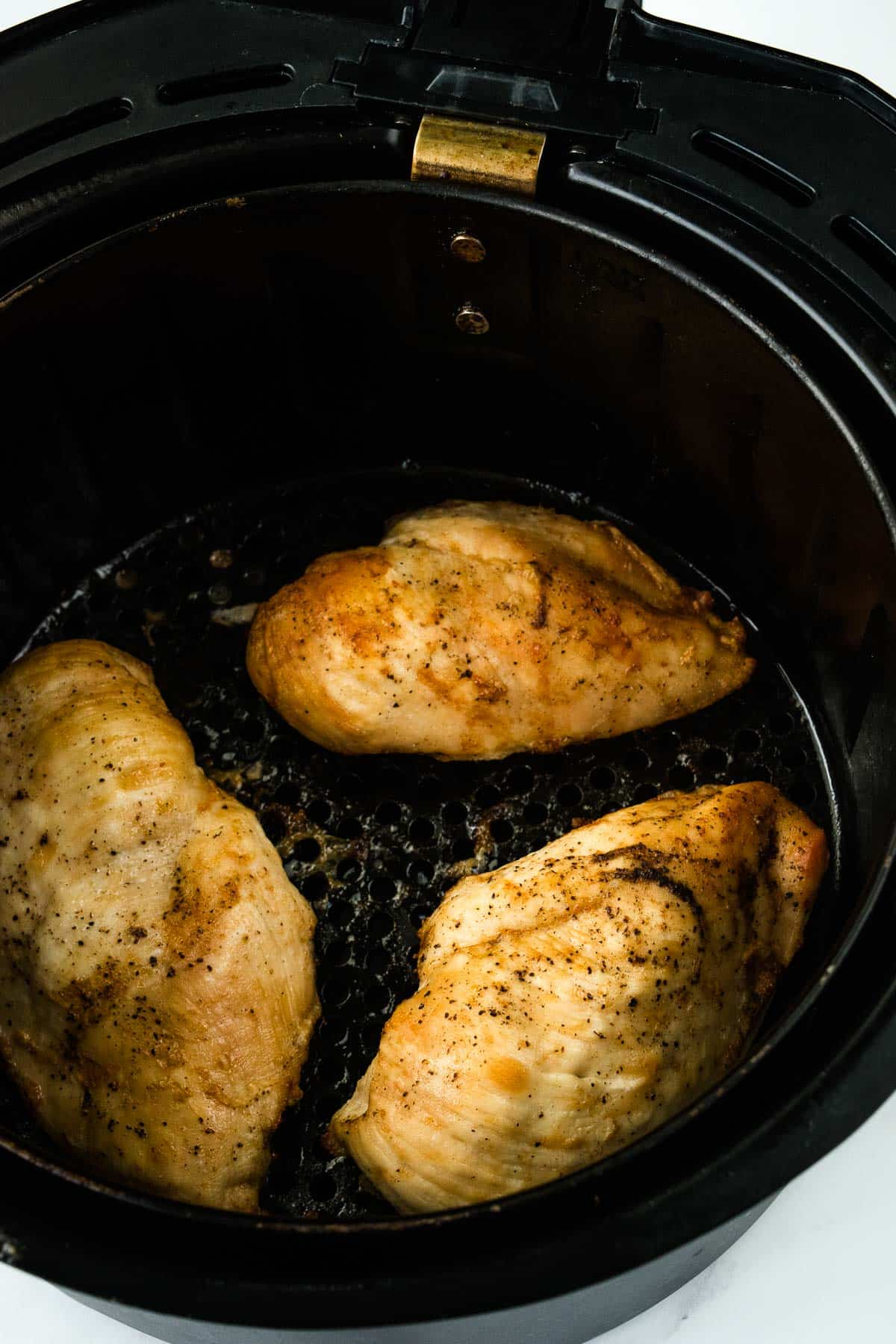 Chicken breasts in an air fryer.