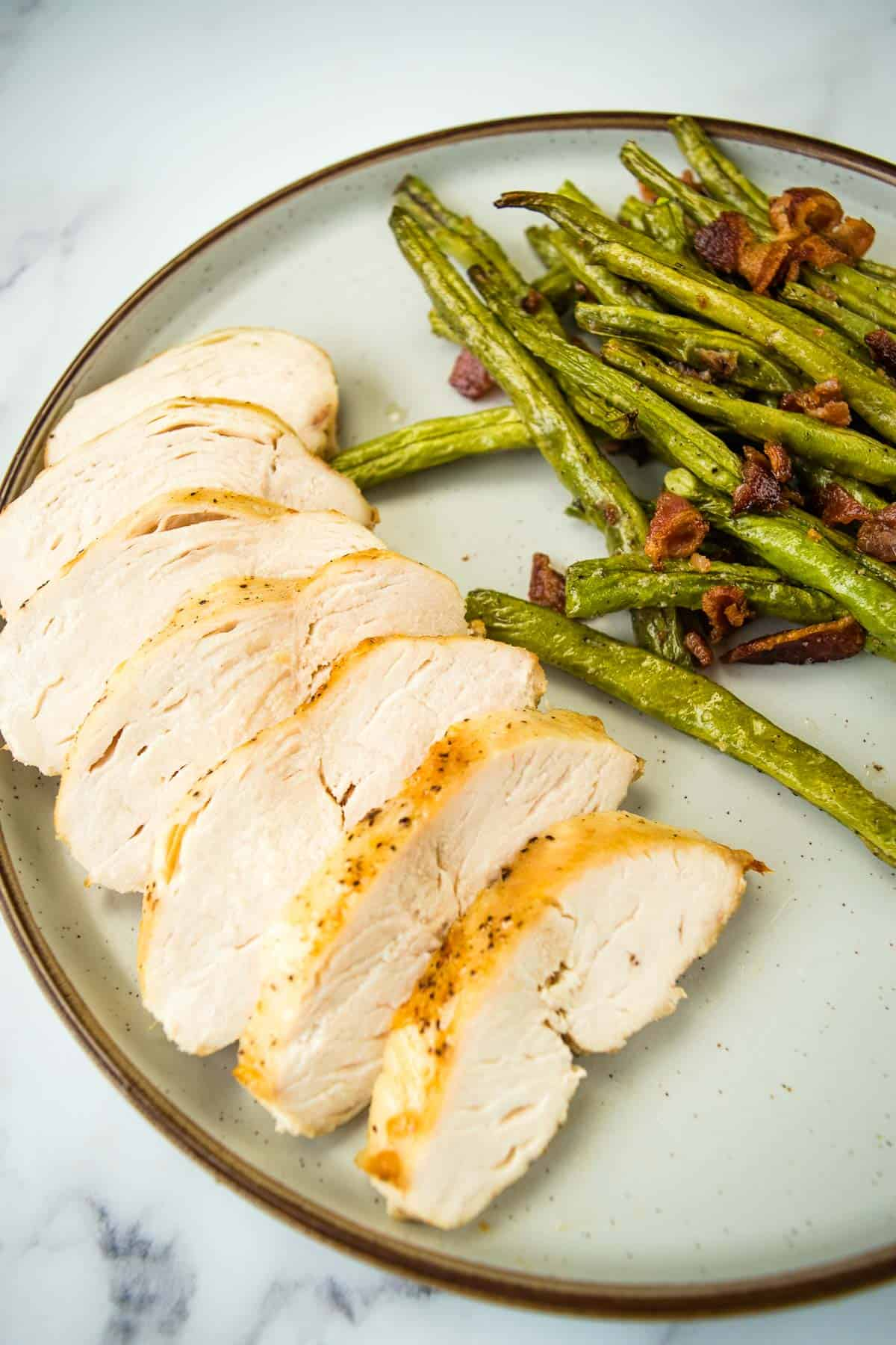 Sliced chicken breast with green beans.