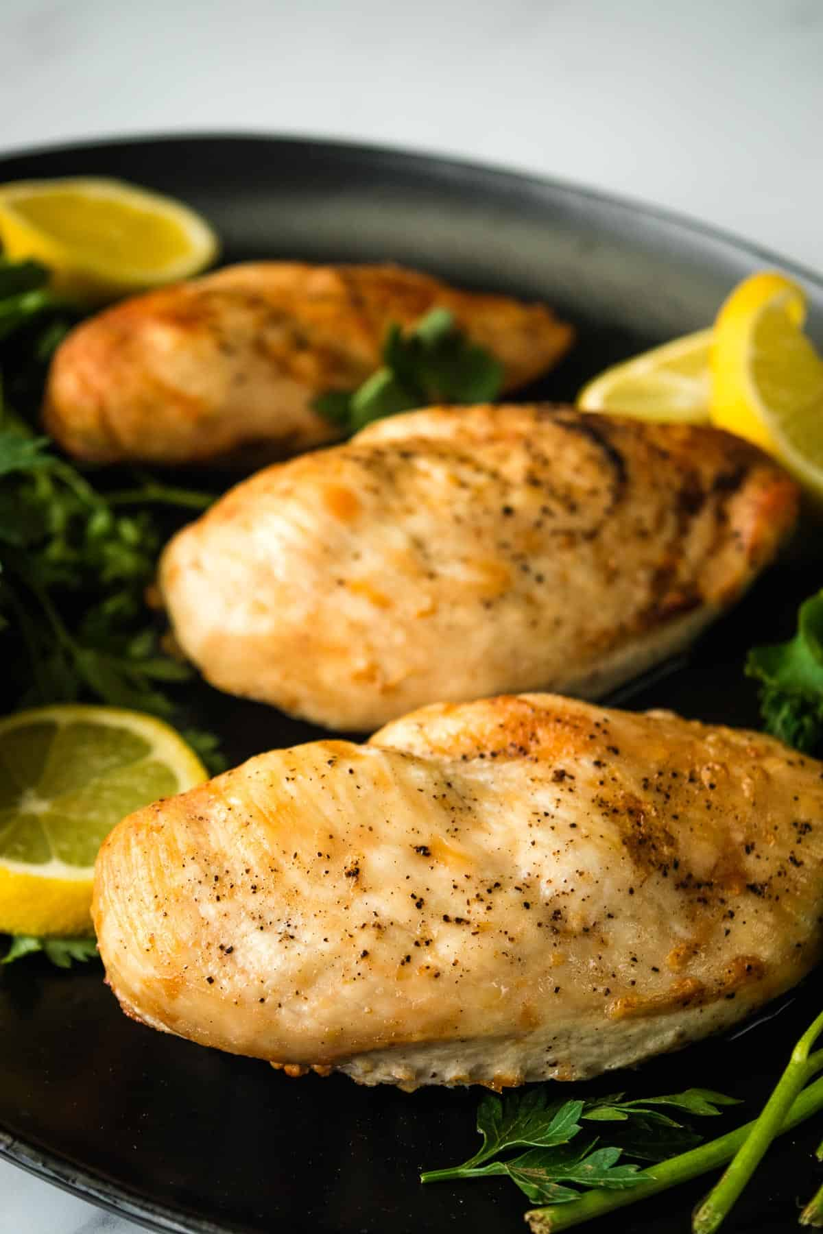 Juicy chicken breasts on a plate with parsley.