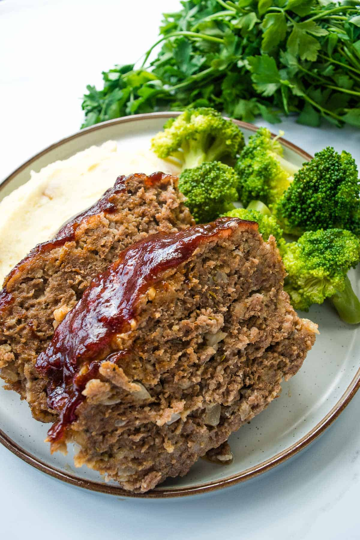 BBQ Meatloaf slices with broccoli and mashed potatoes.