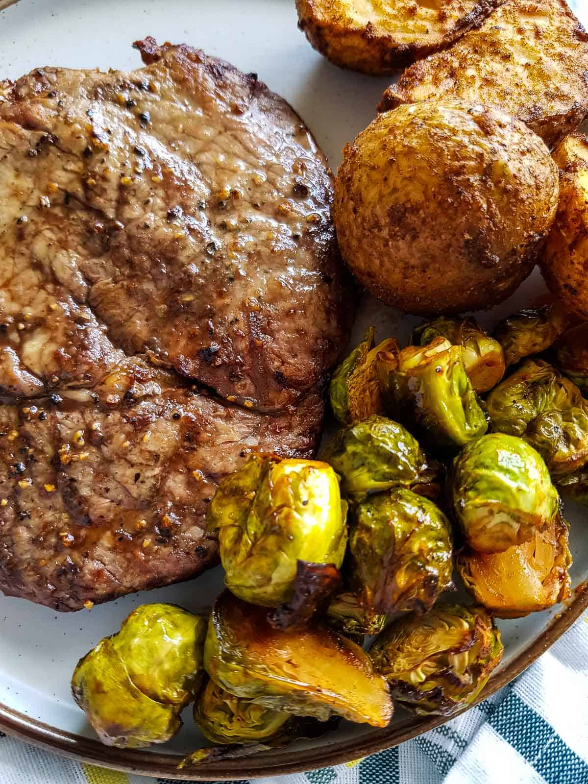 Brussels sprouts on a plate with steak and potatoes.
