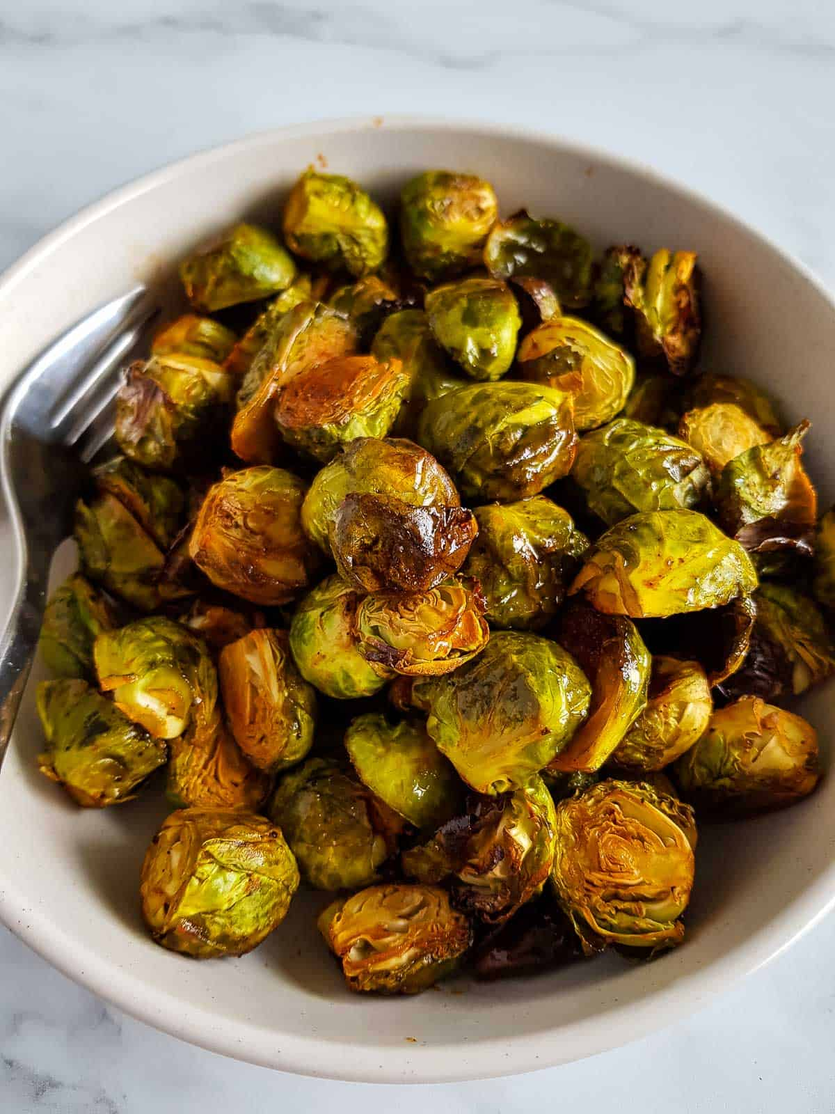 Honey Sriracha Brussels Sprouts in a bowl with a fork.