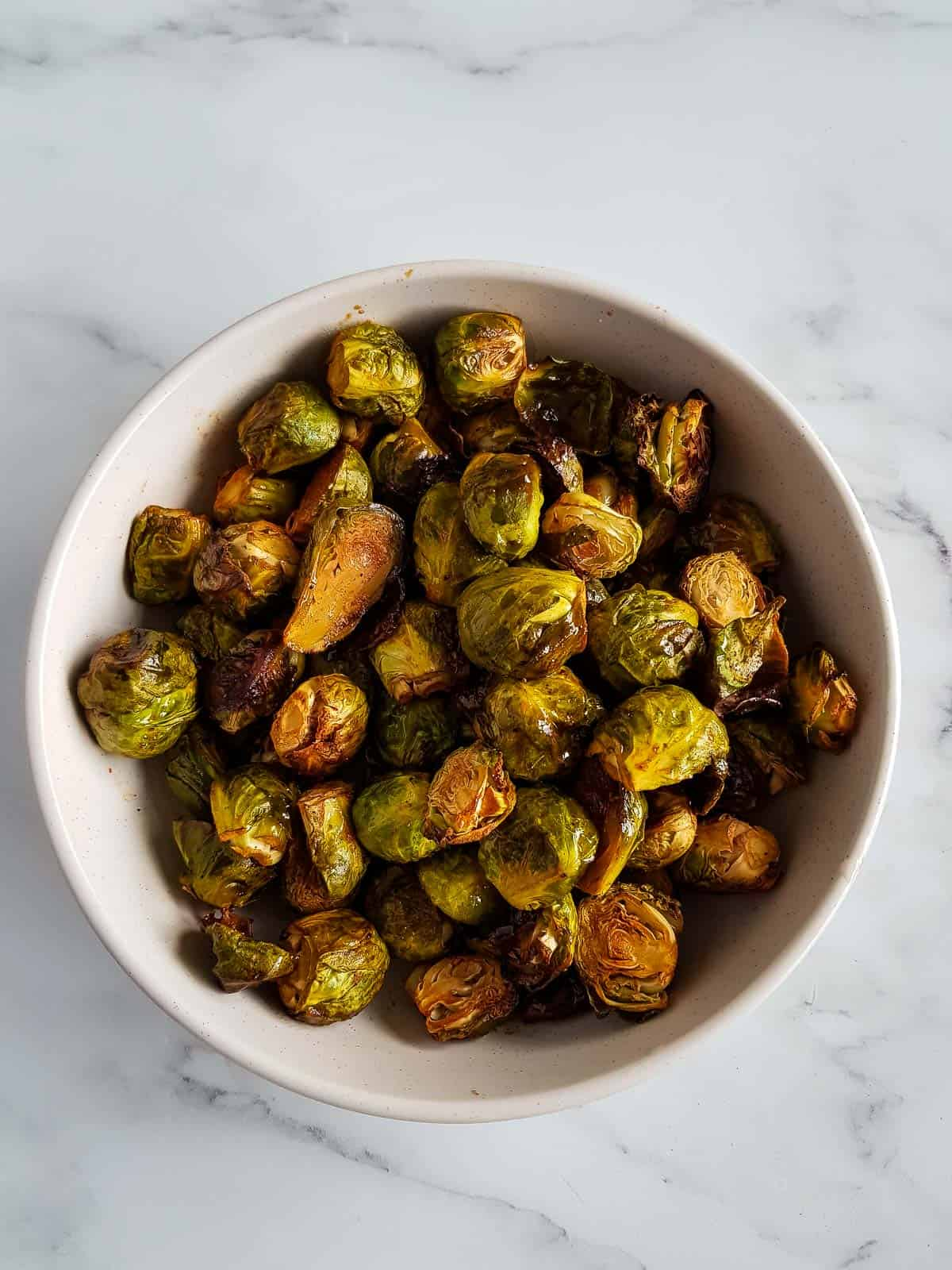 Brussels sprouts with honey and sriracha in a bowl.