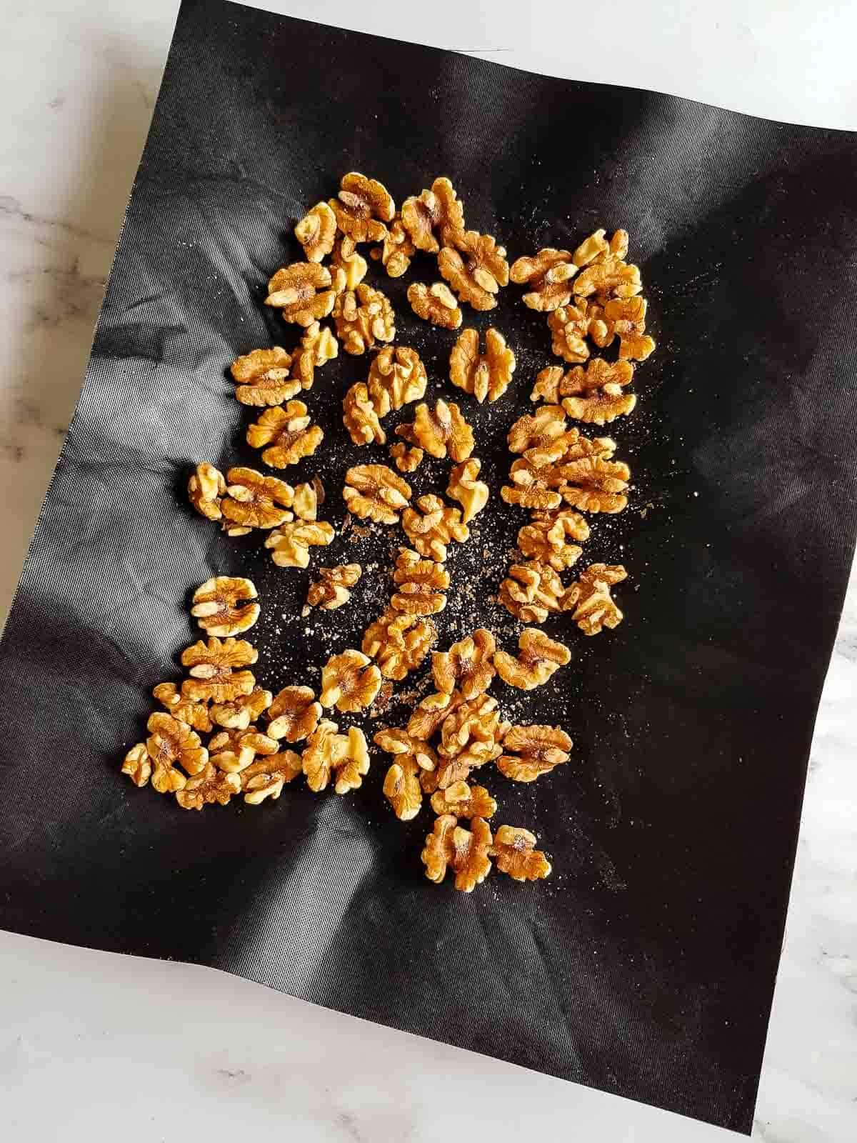 Roasted walnuts on a baking sheet.