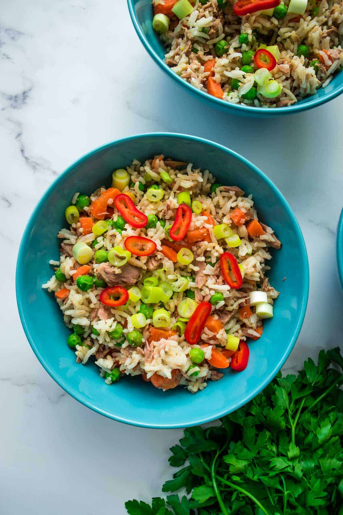 A bowl of fried rice with tuna, carrots, peas and chili.