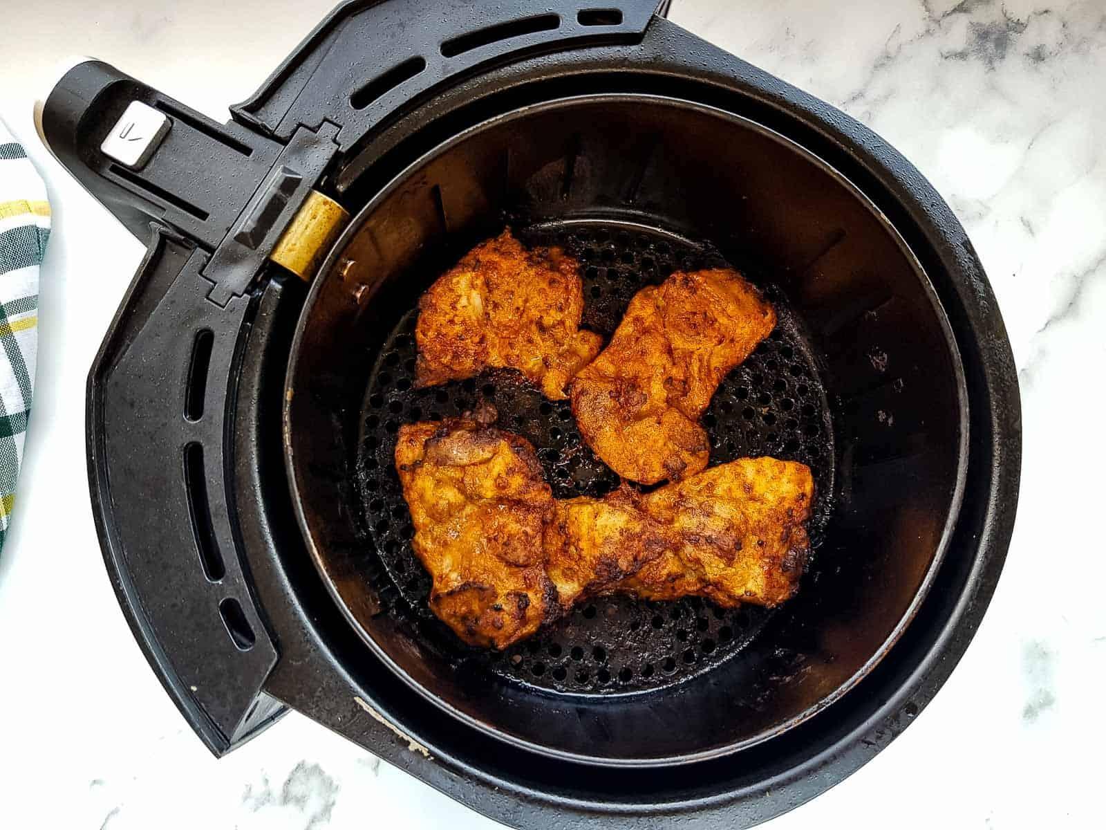 Chicken thighs in an air fryer.
