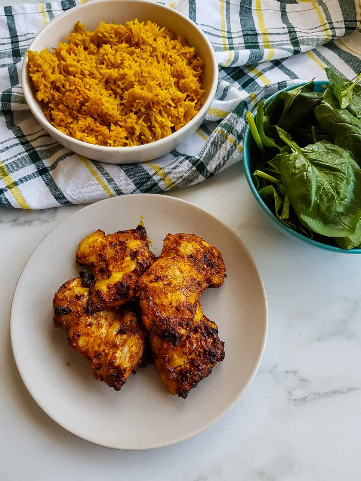 Chicken thighs on a plate with rice and salad in the background.