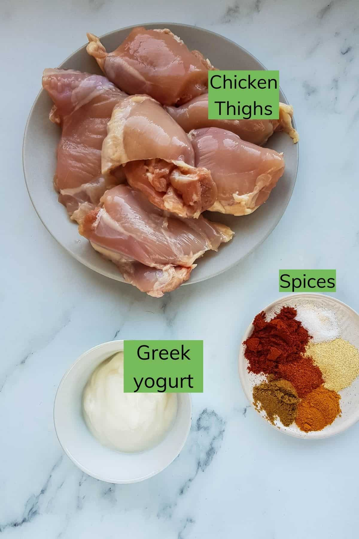 Greek yogurt, chicken thighs and spices laid out on a table.