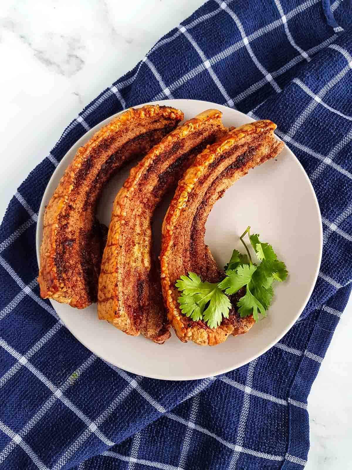Crispy sliced pork belly with crackling on a plate.