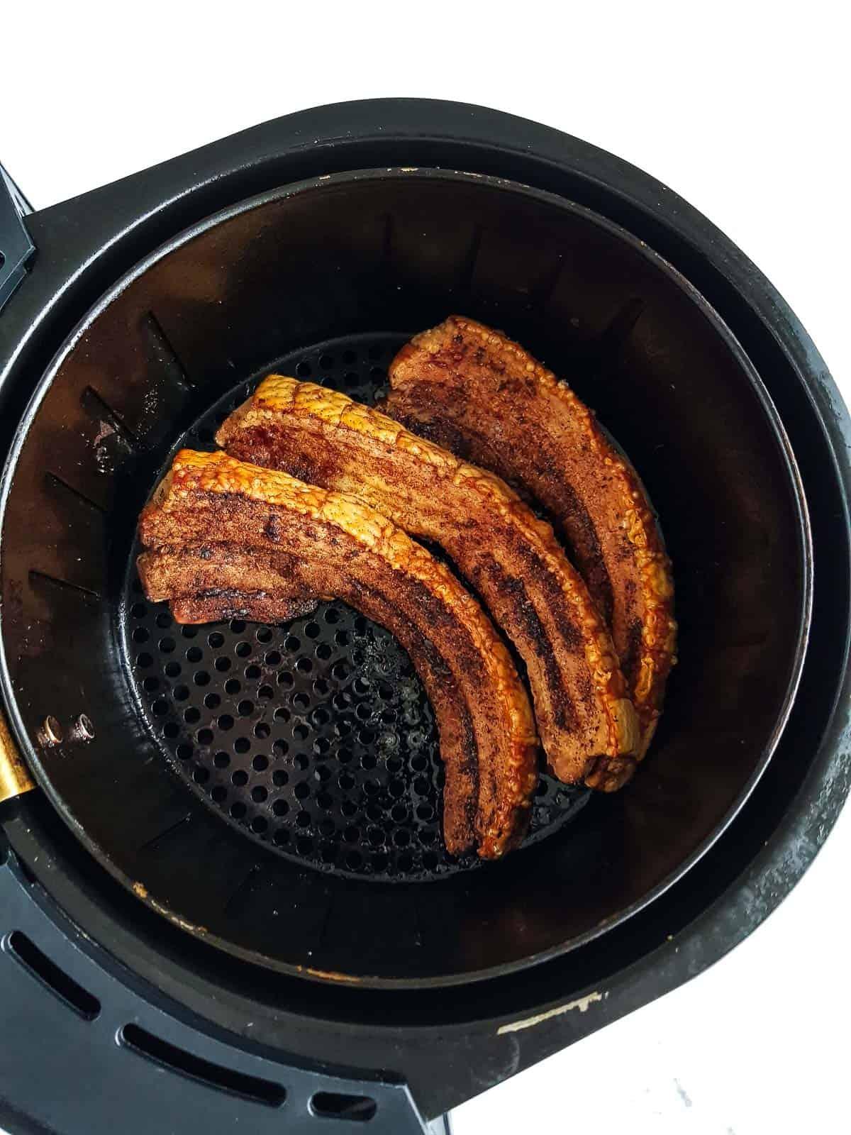 Pork belly slices in an air fryer basket.