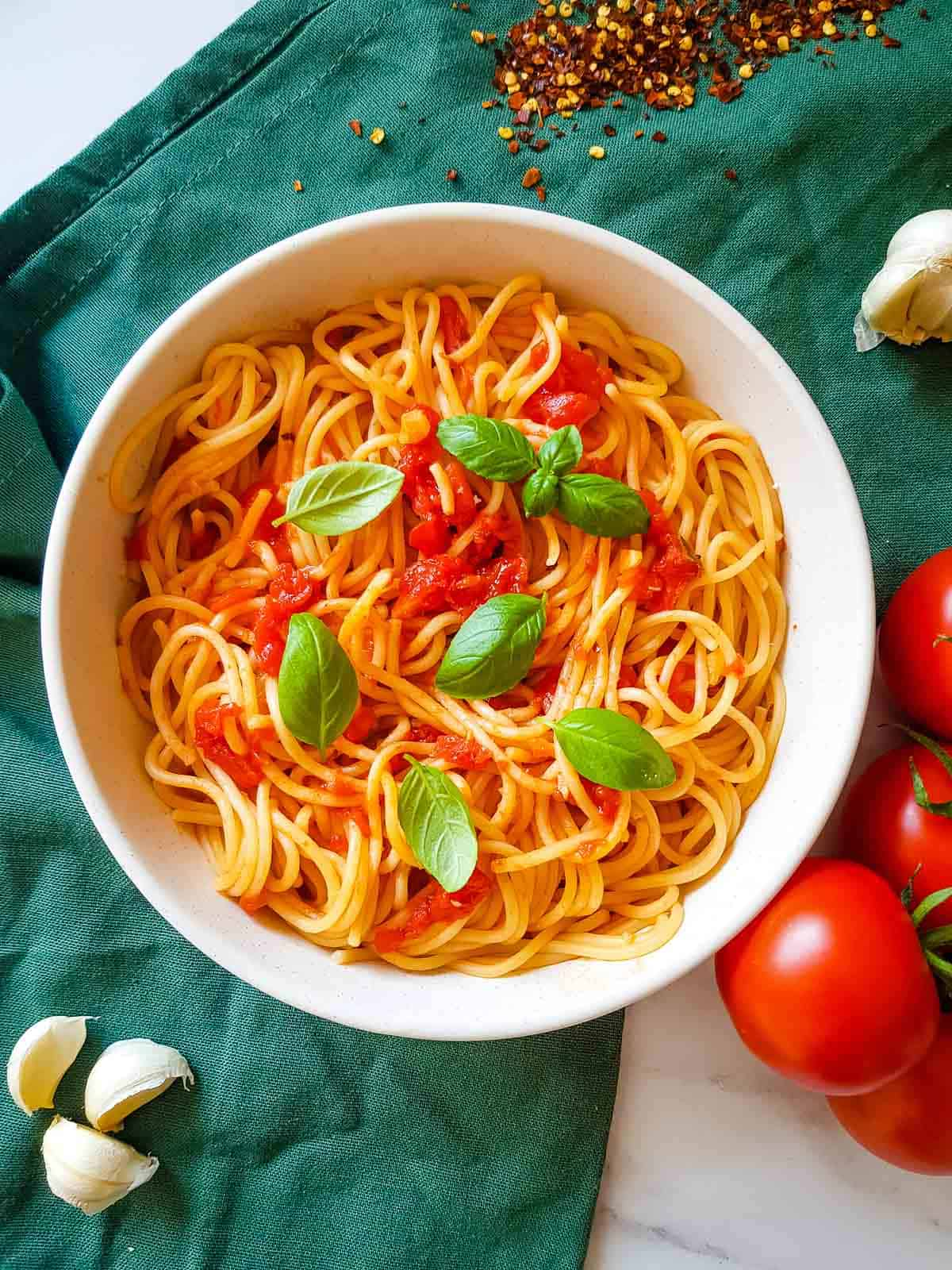 Arrabbiata spaghetti in a bowl with basil leaves on top.