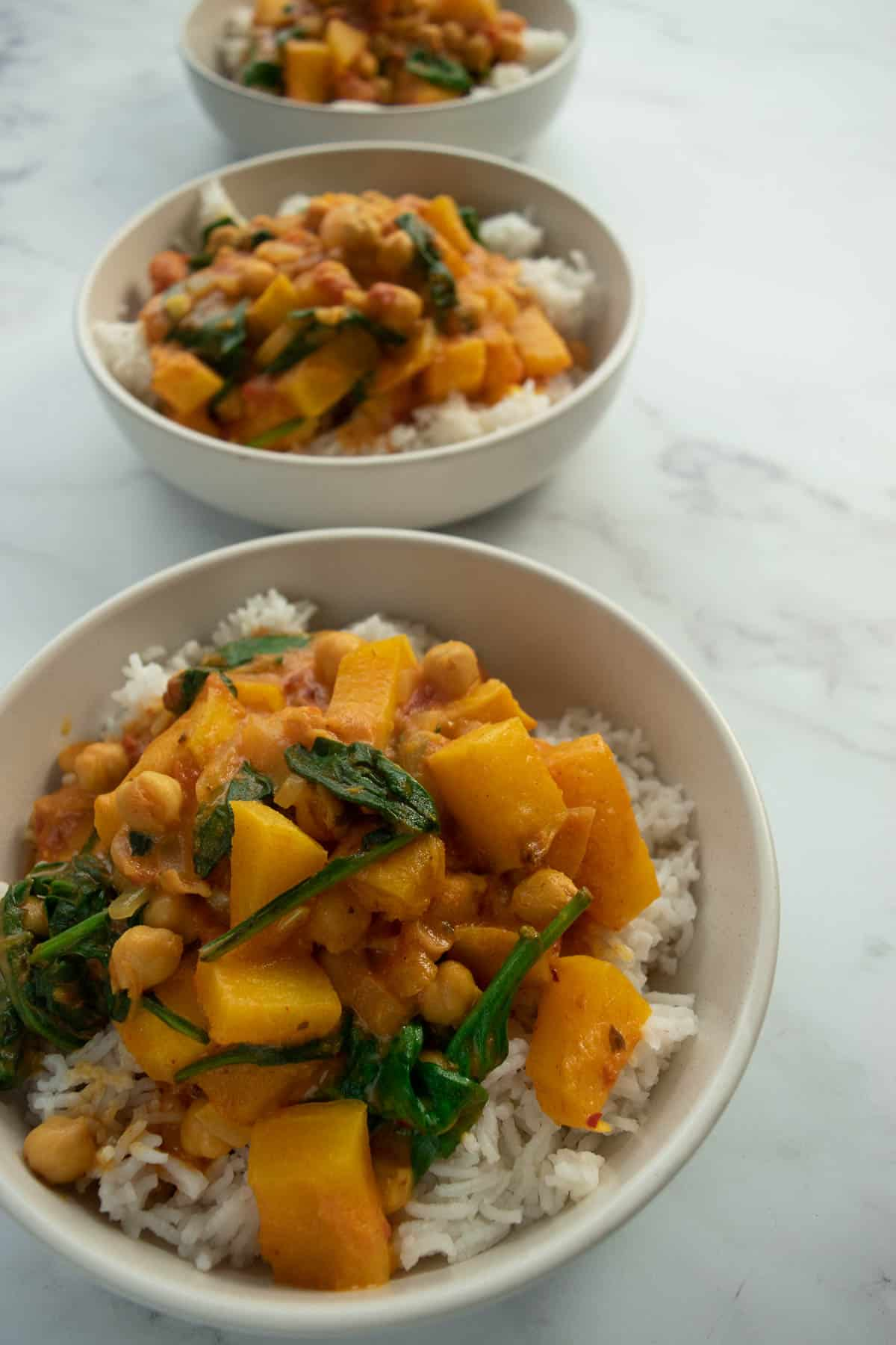 Bowls of butternut squash chickpea curry and rice.