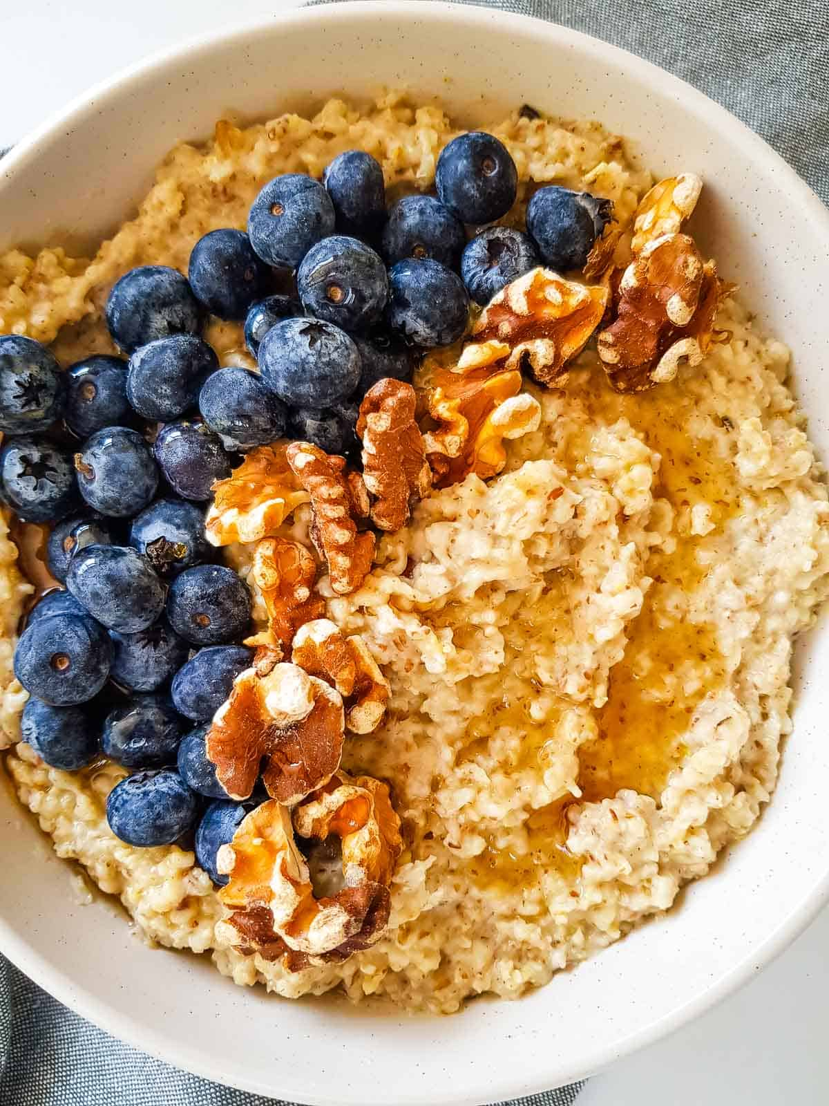 A white bowl with oatmeal, blueberries and walnuts.