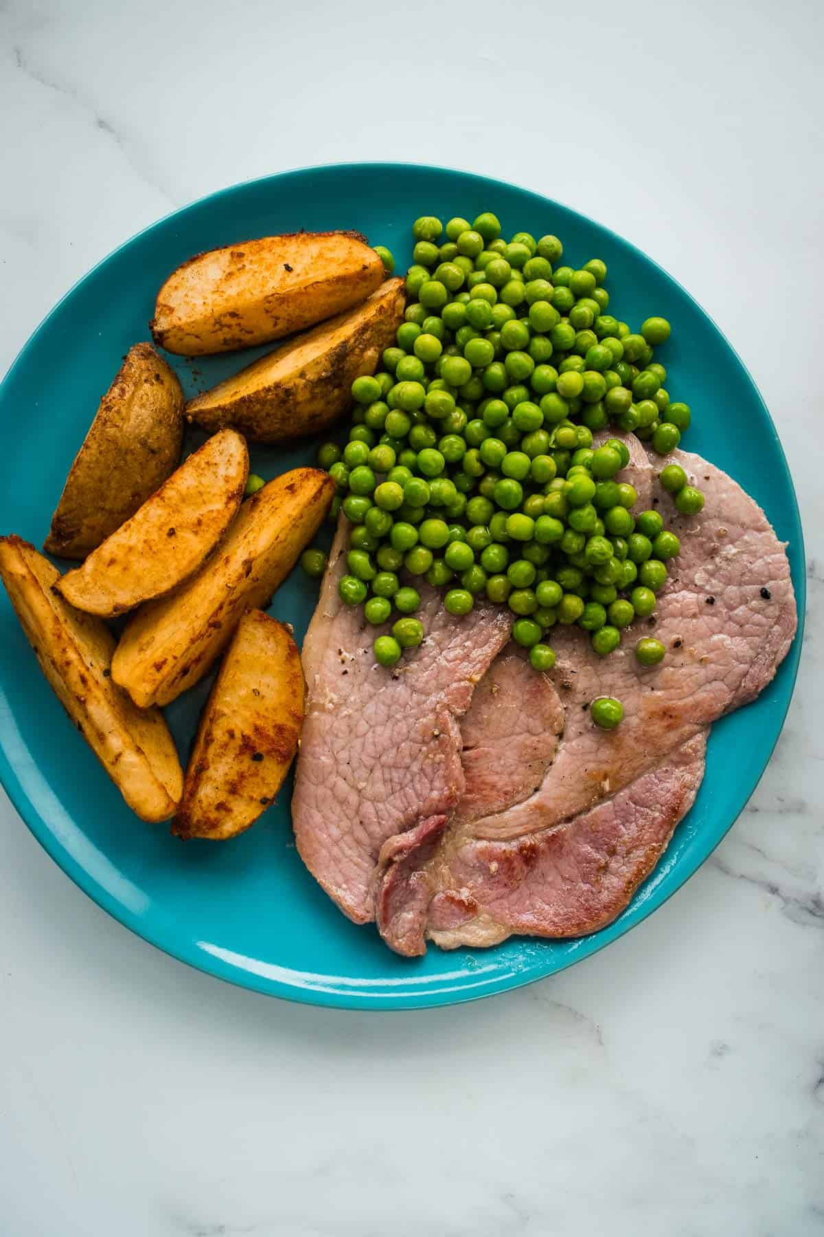 Gammon steaks on a plate with potato wedges and peas.
