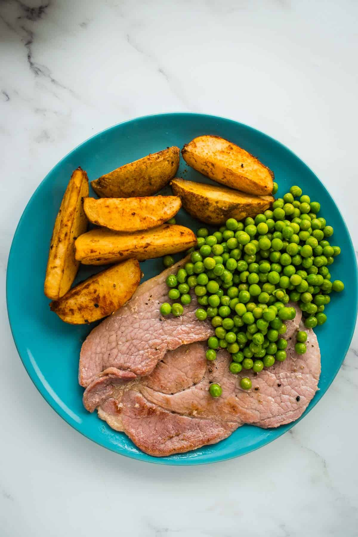 Ham steaks with peas and potatoes.