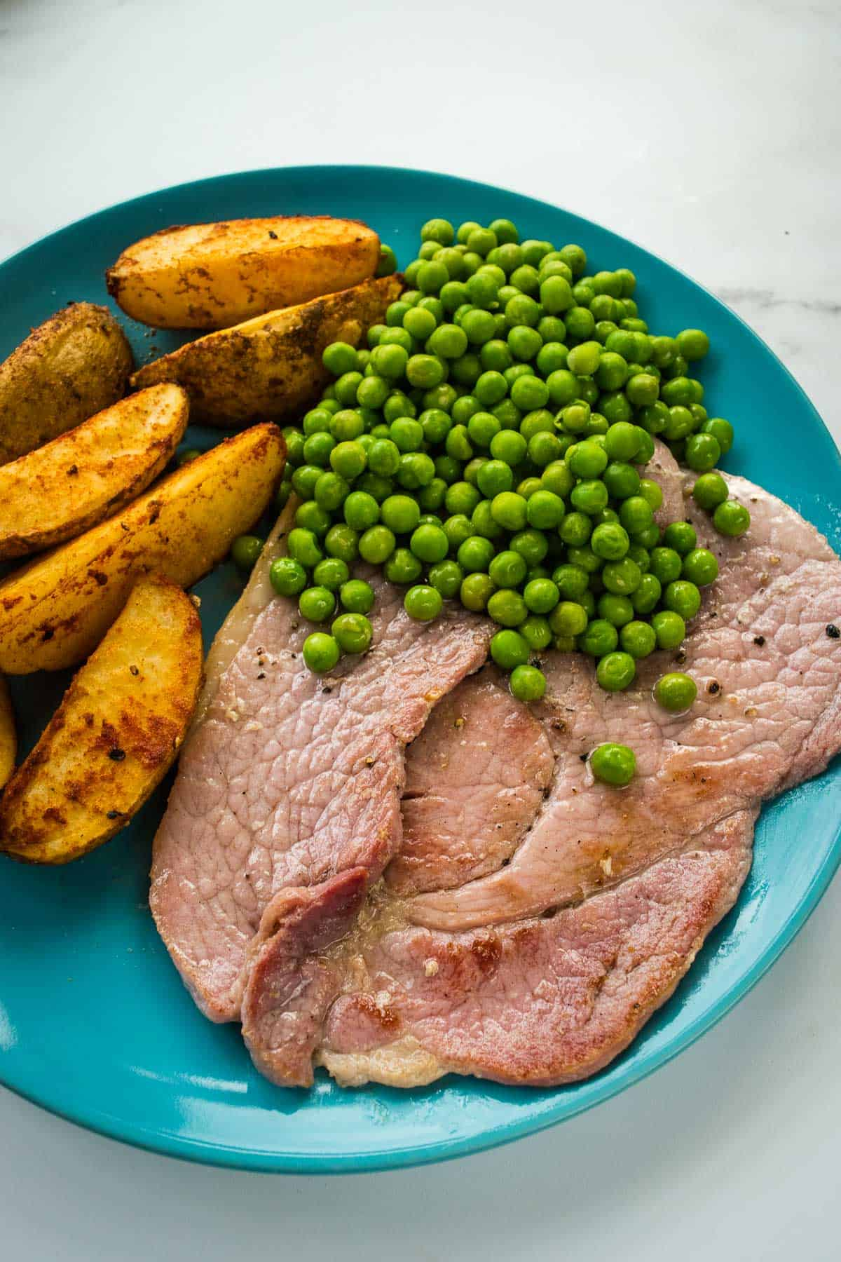Plated ham steaks with side dishes.