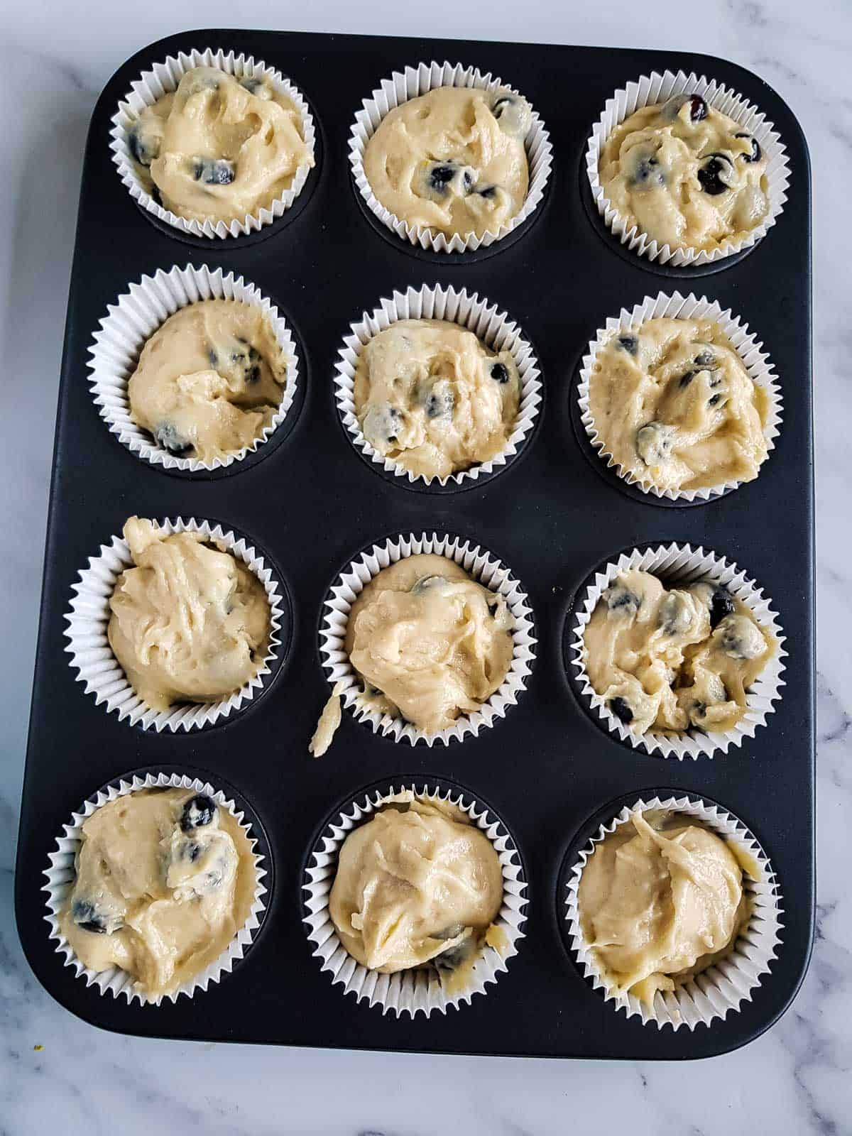 Muffin batter added to lined muffin pan.