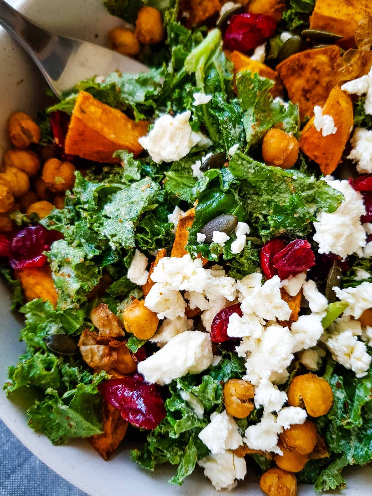 Close up of kale, chickpeas and sweet potato salad with feta cheese.