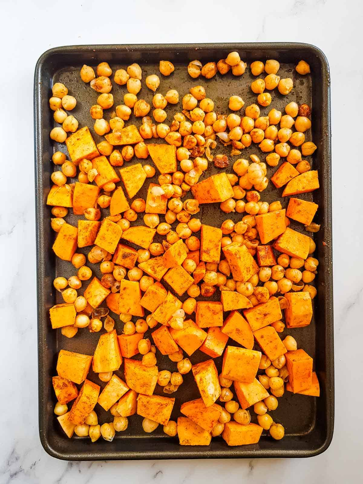 Sweet potatoes and chickpeas on a sheet pan.
