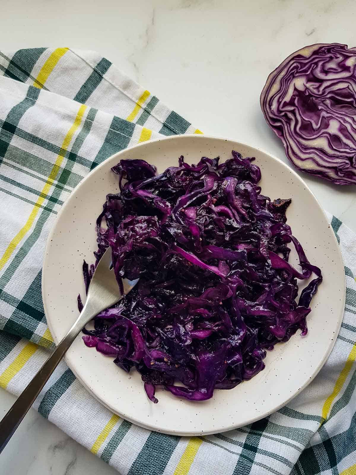 Braised red cabbage on a plate with a fork.