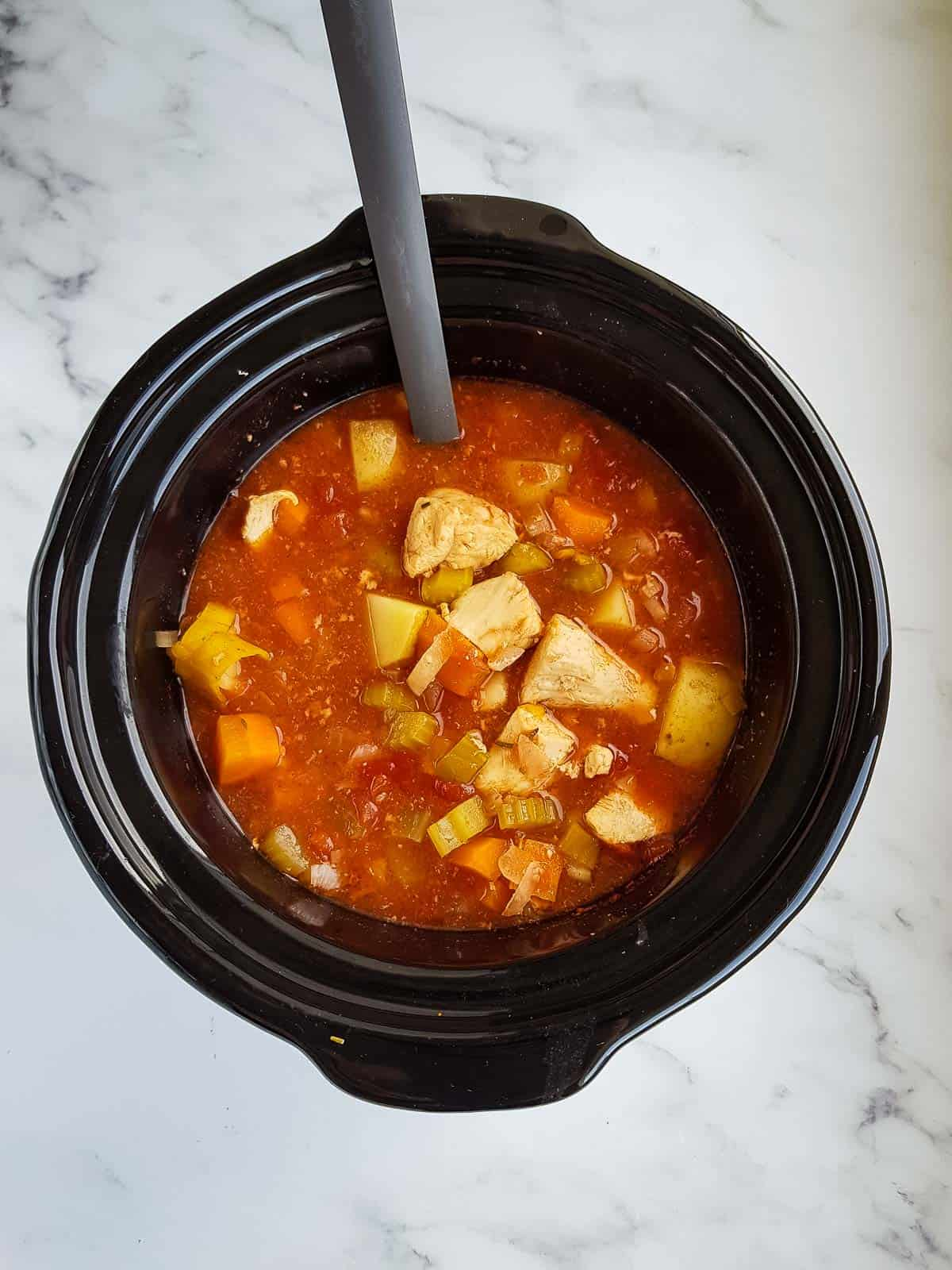 Cooked chicken stew in a slow cooker.