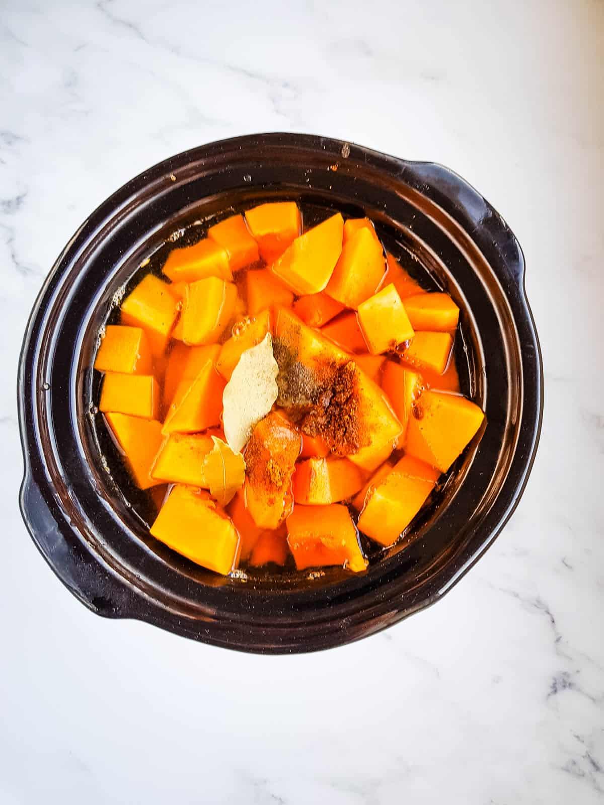 Pumpkin soup ingredients in a slow cooker.