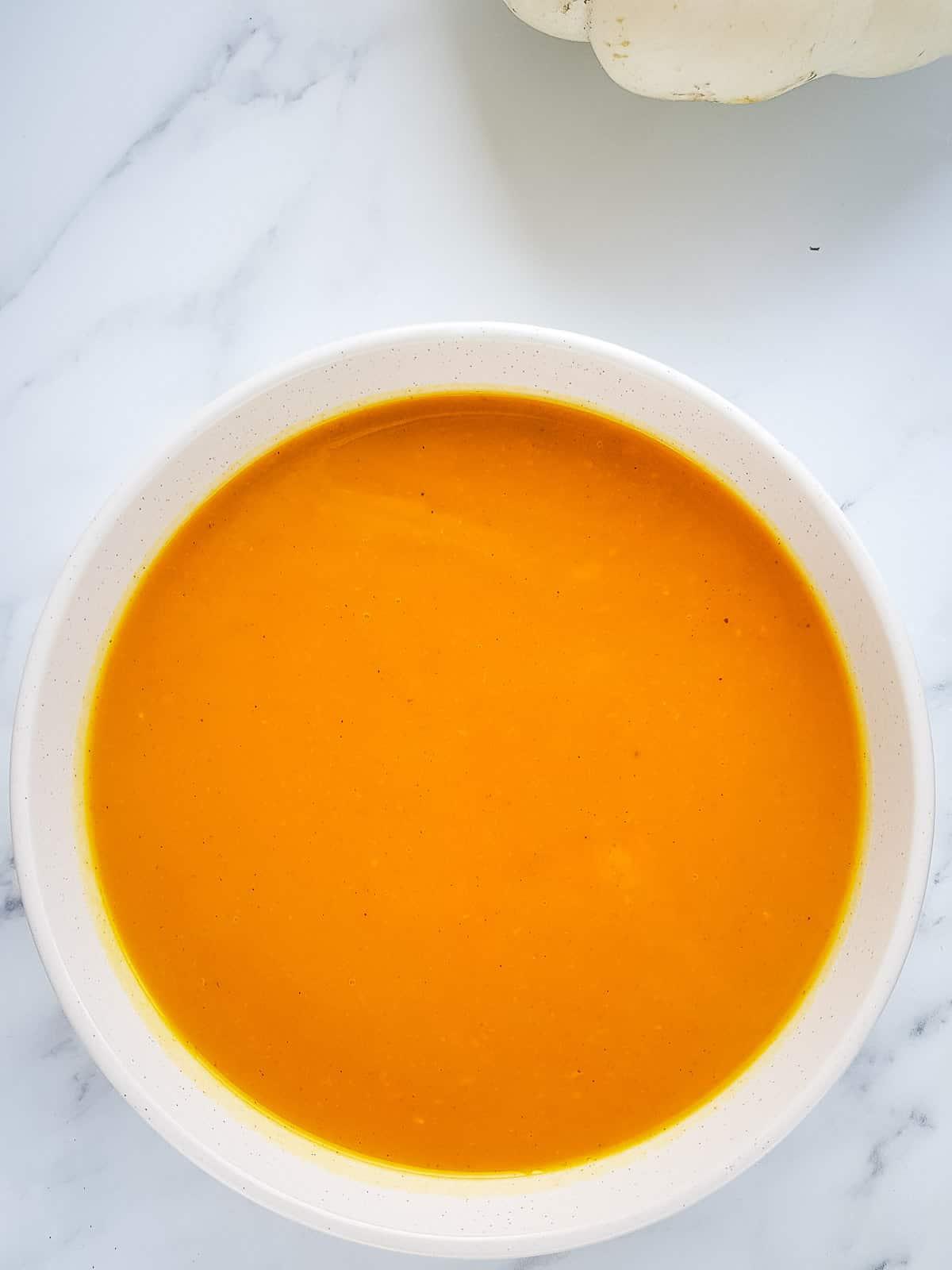 A white bowl with pumpkin soup.