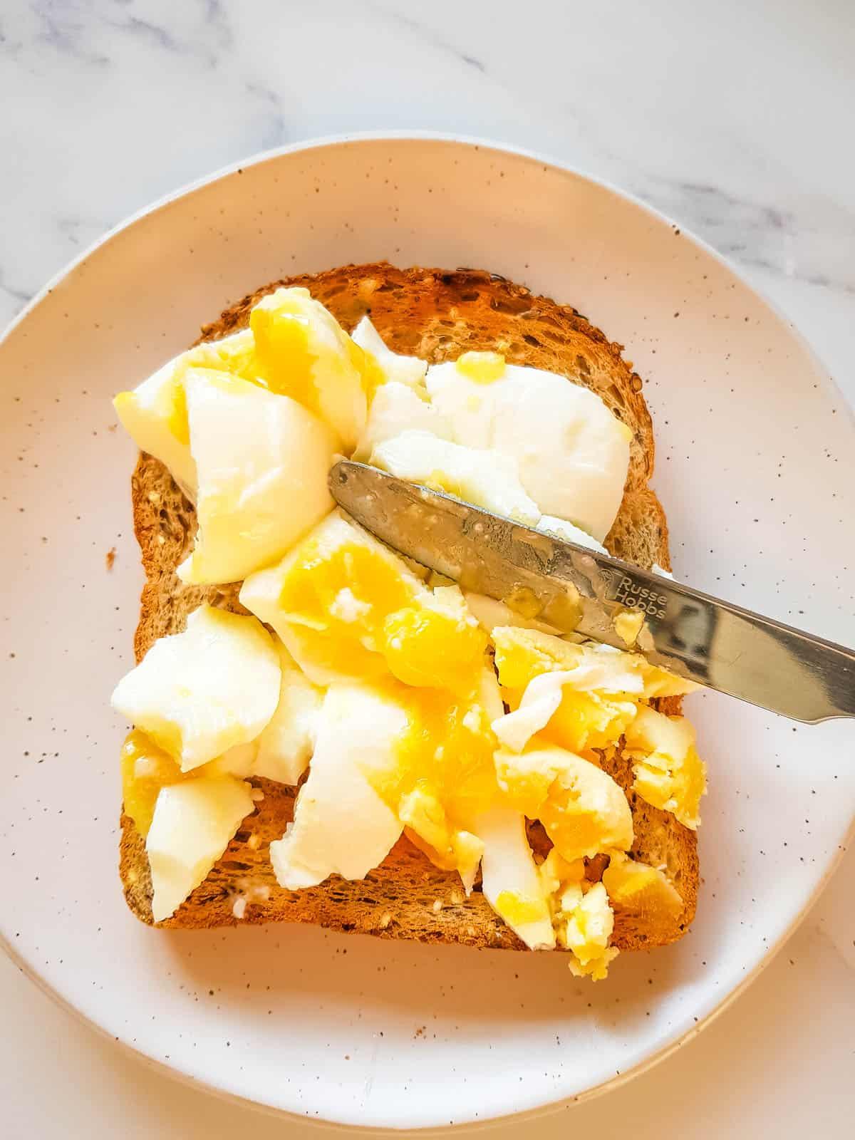Smashing an egg on toast.