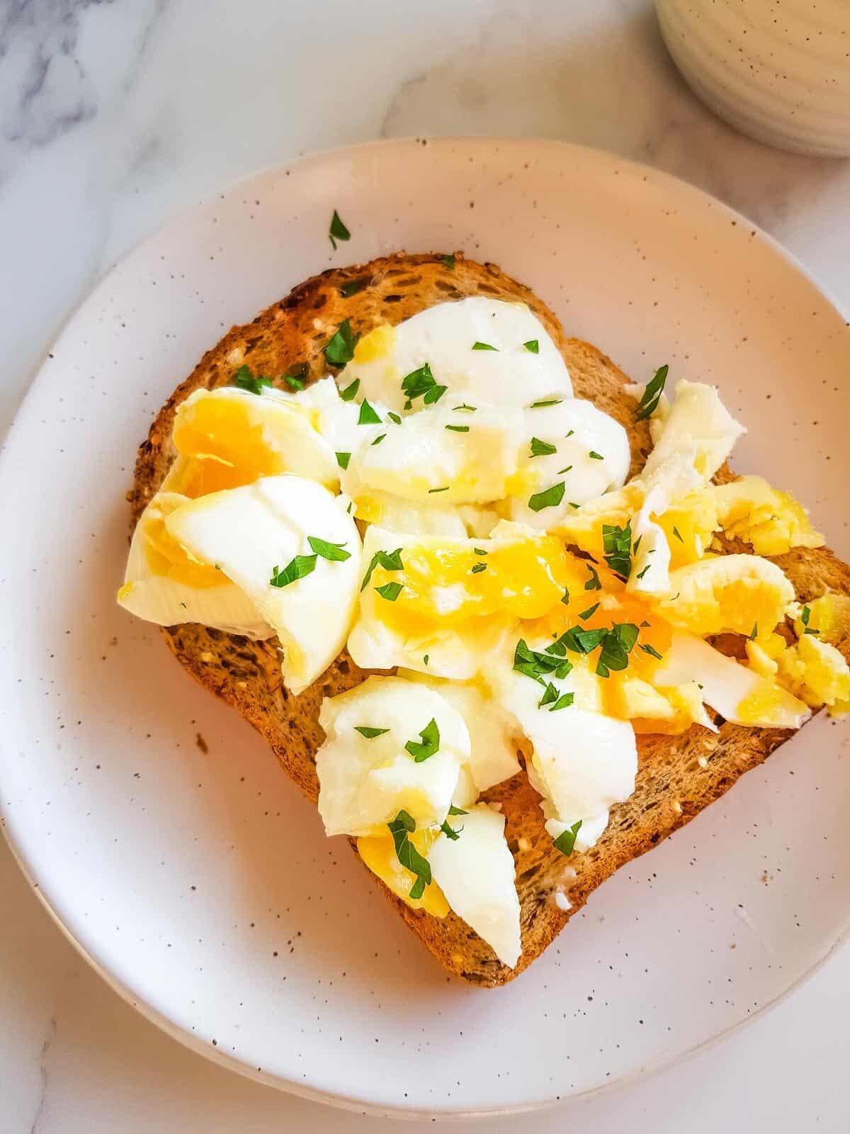 Smashed egg on toast with parsley.