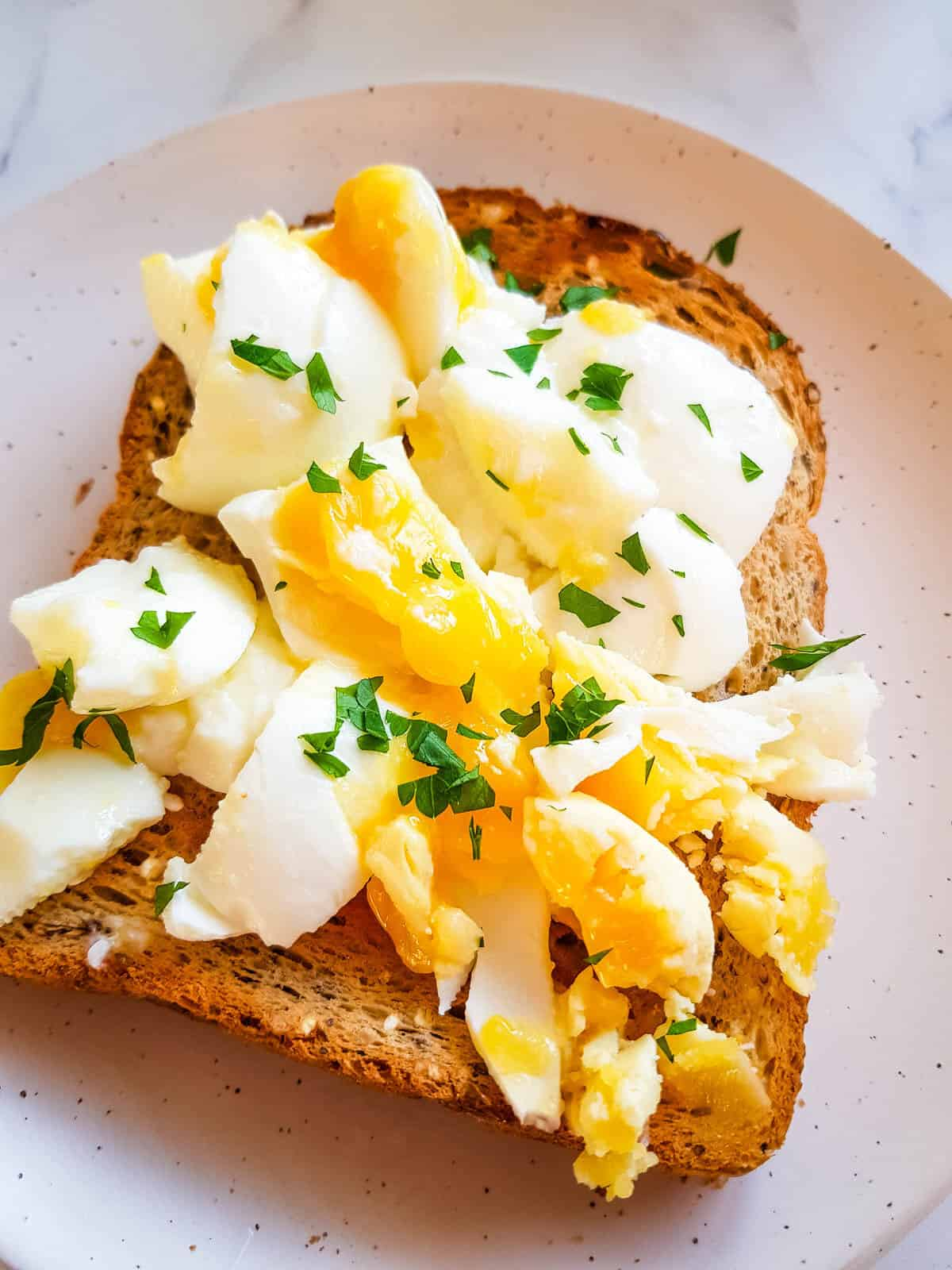 Toast with smashed egg and parsley.