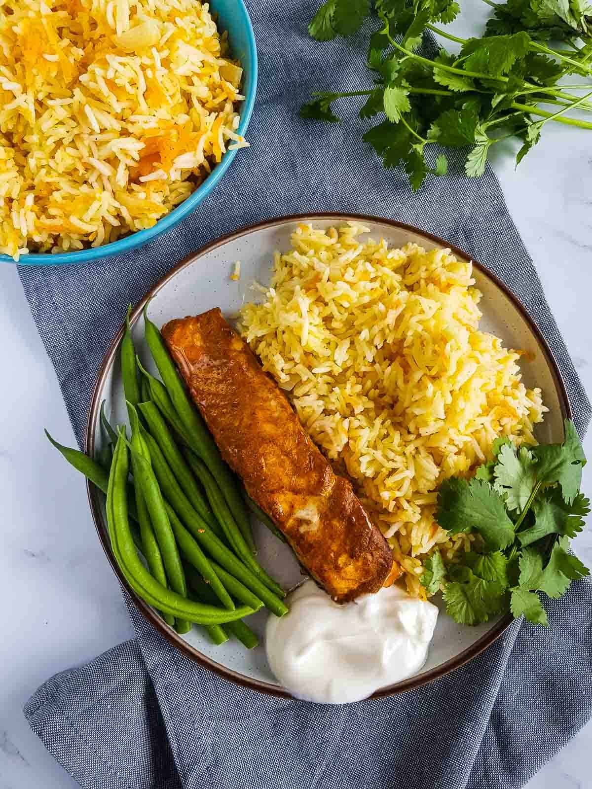 A dinner plate with tandoori marinated salmon.