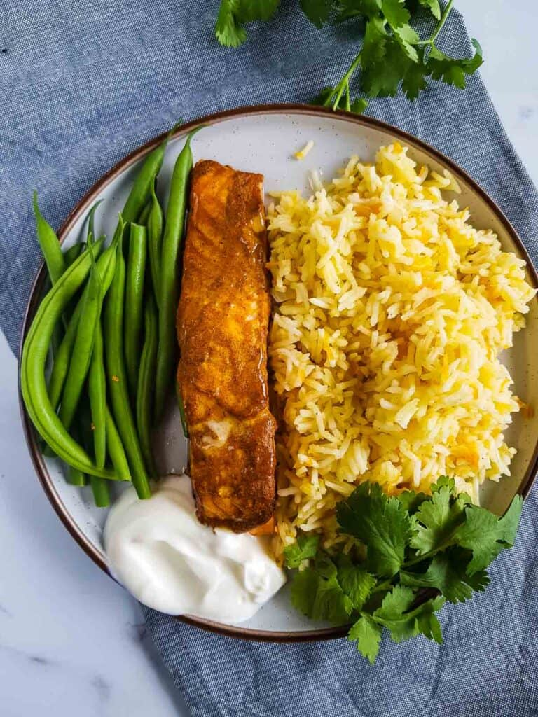 A plate with tandoori salmon, carrot rice and green beans.