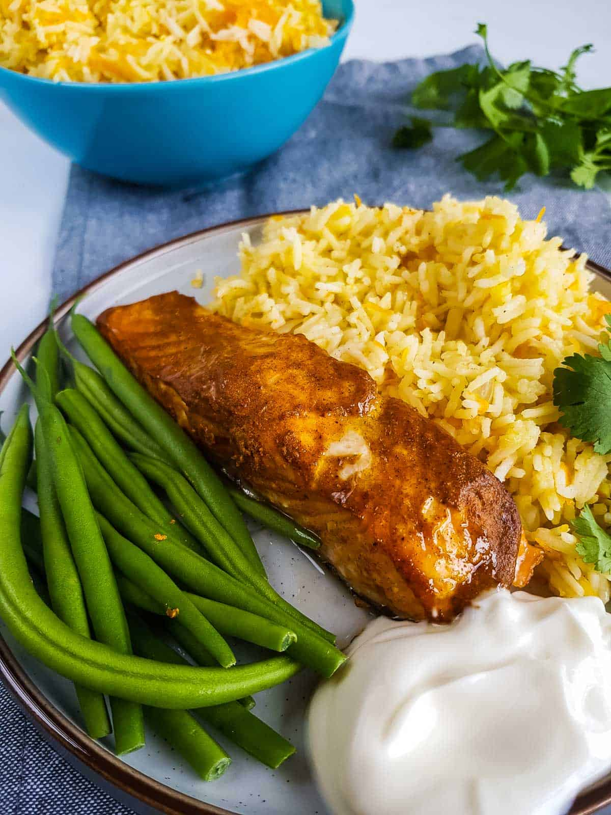 Tandoori salmon on a plate with rice and green beans.