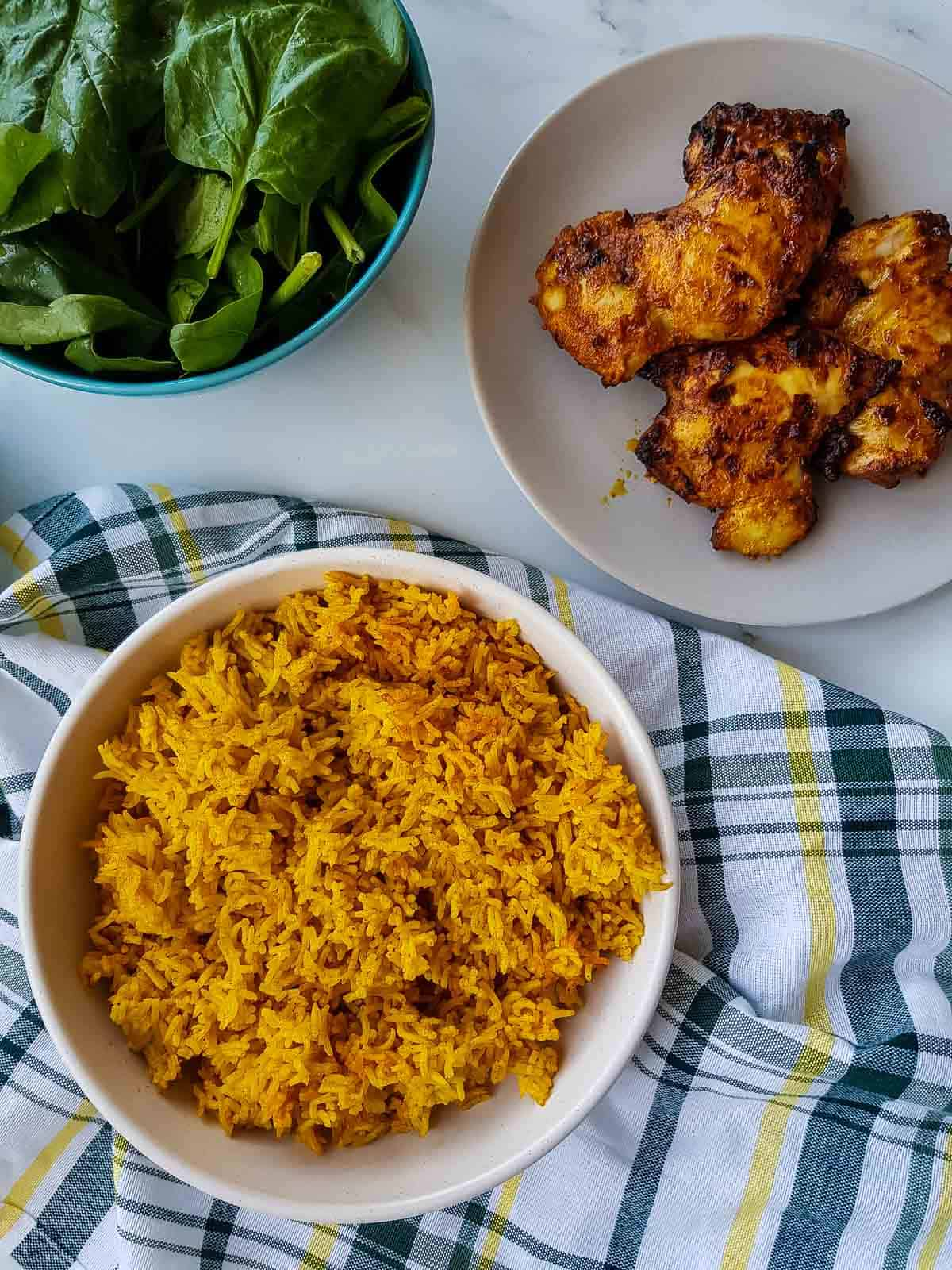 Rice in a bowl with chicken and salad on the side.