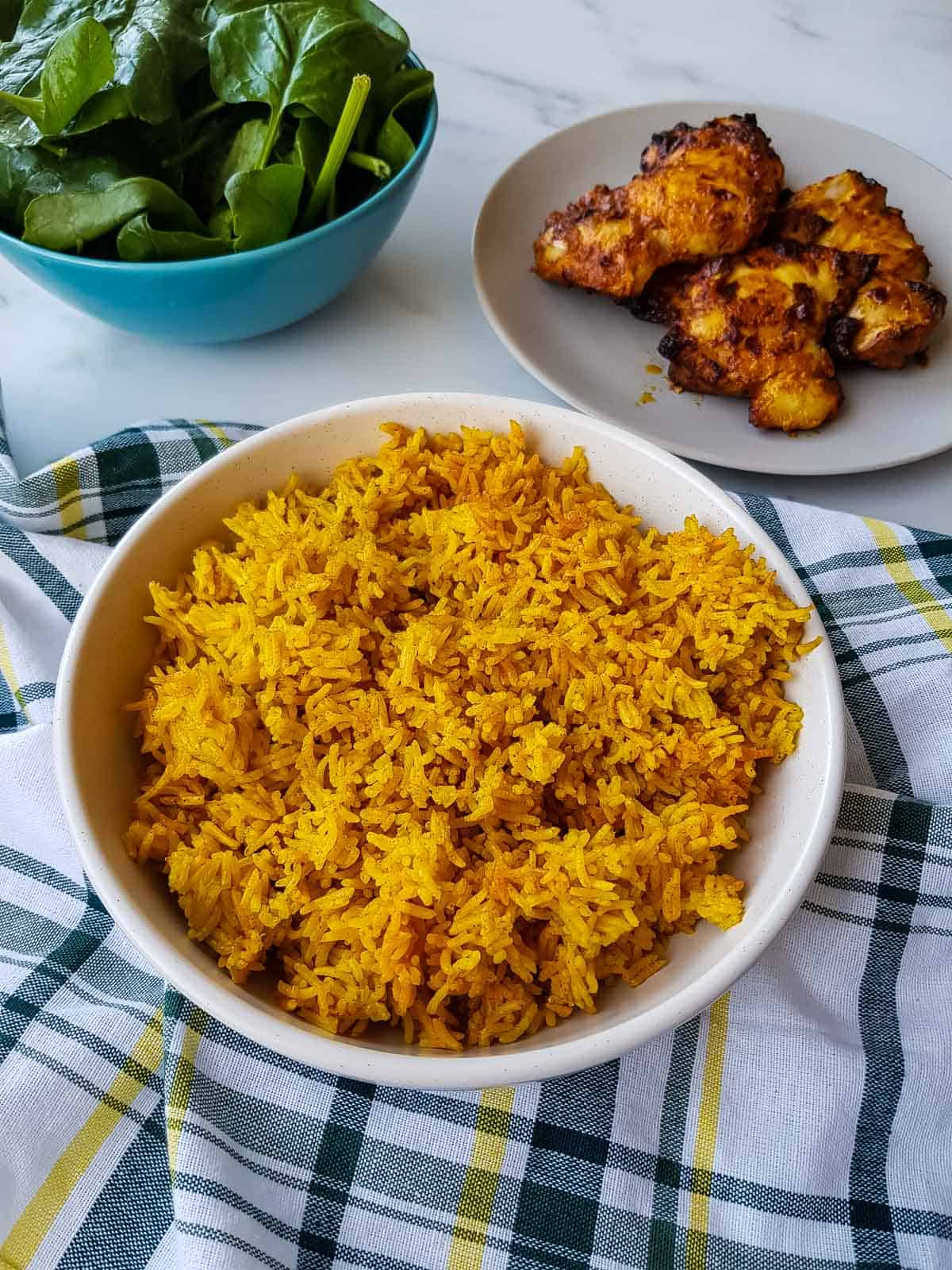 Turmeric rice on a table with chicken and salad.