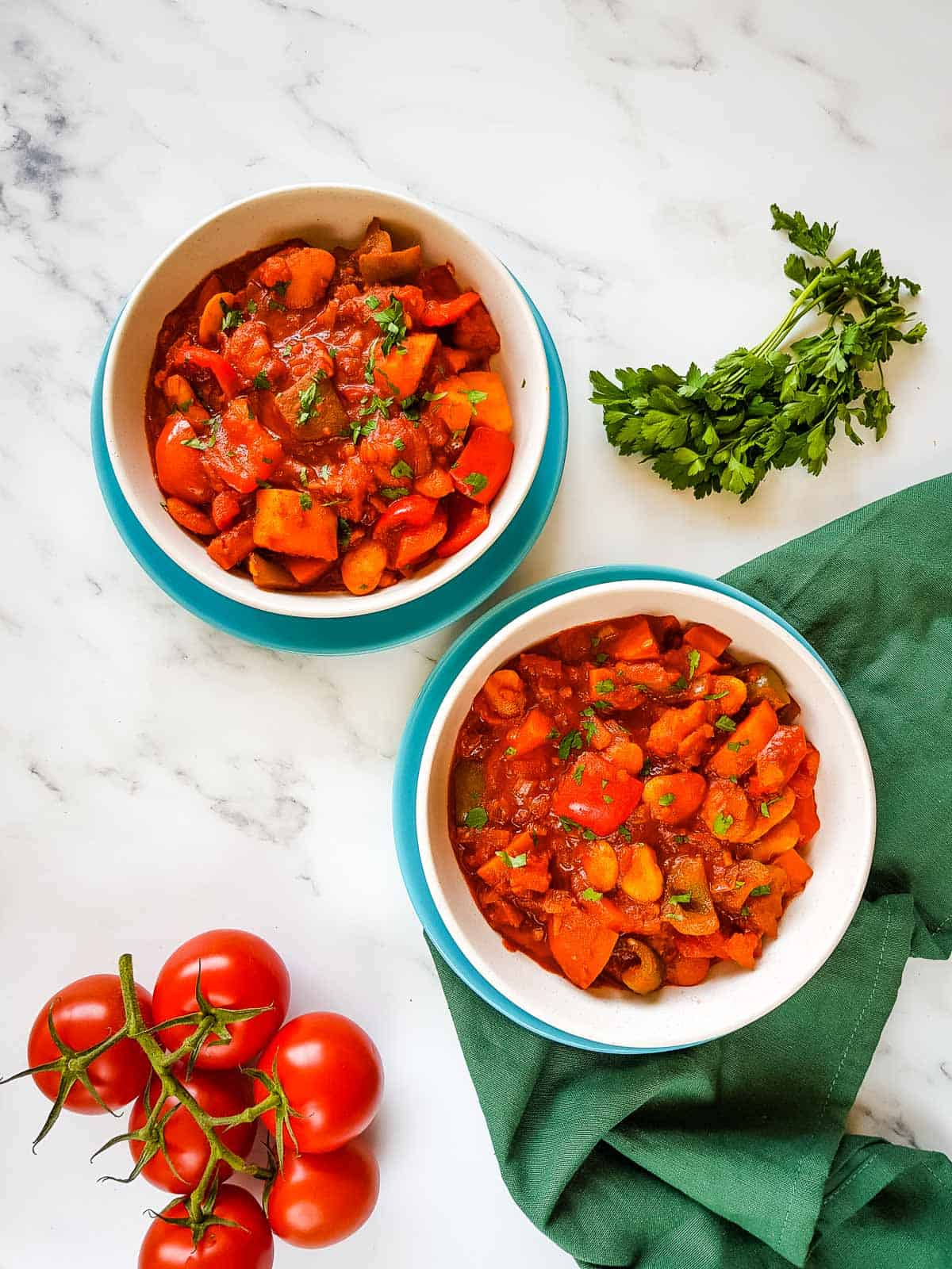 Vegetable goulash in bowls with parsley and tomatoes on the side.