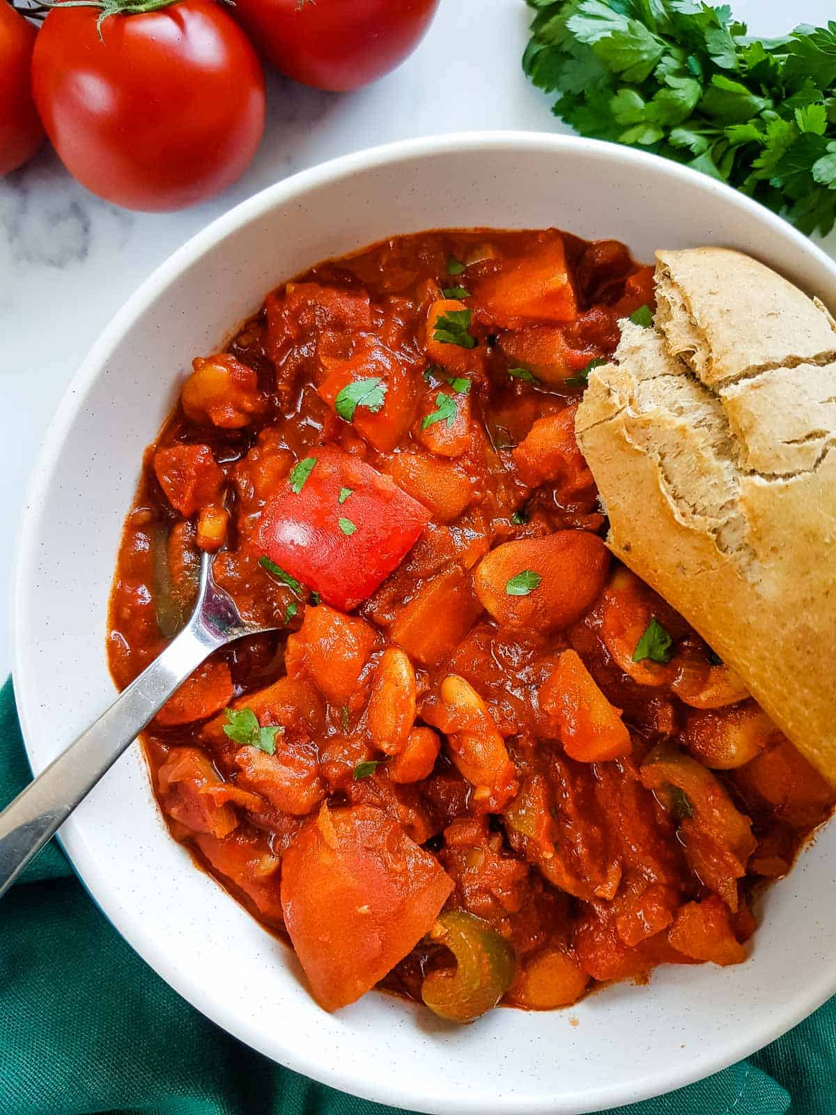 Goulash in a bowl with a spoon in it, a baguette on the side.