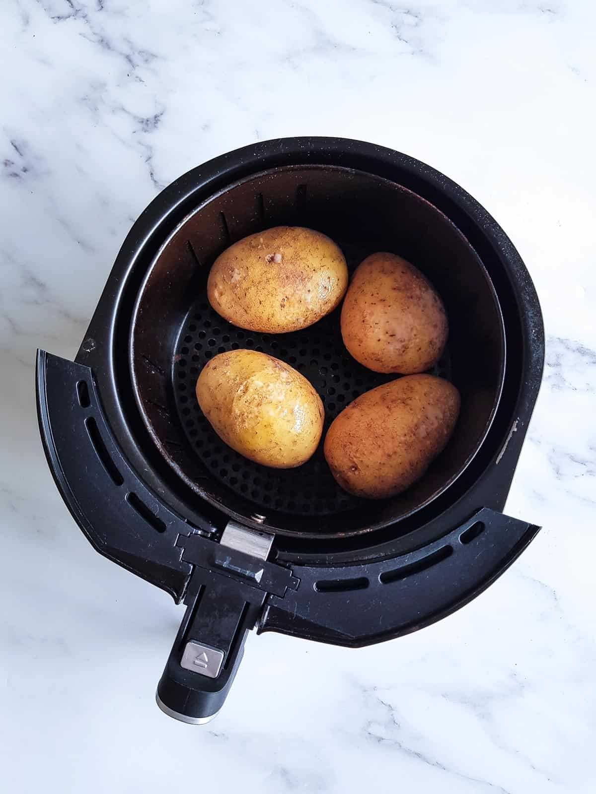 Raw potatoes in an air fryer.