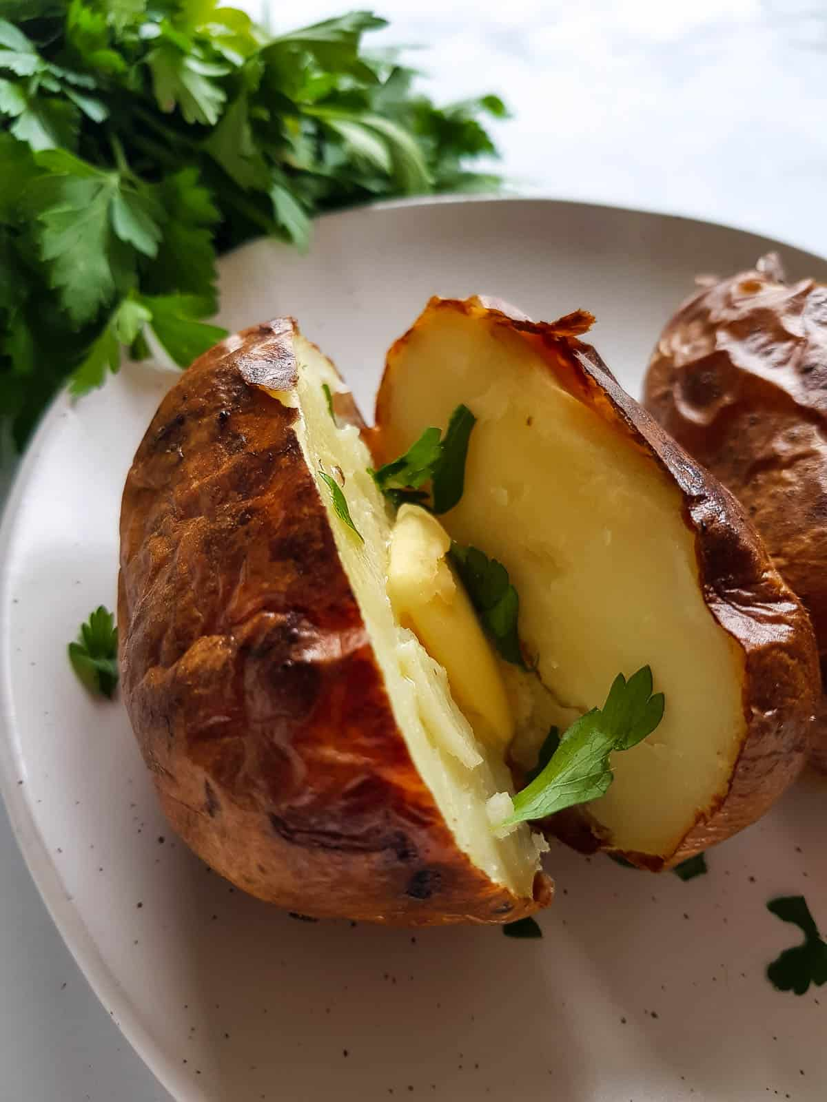 Close up of a baked potato with butter and parsley.