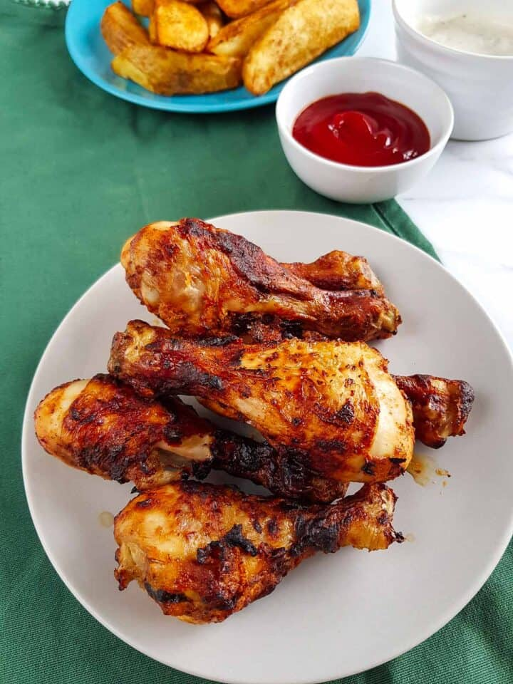 Air fried chicken drumsticks on a plate with potato wedges and ketchup in the background.