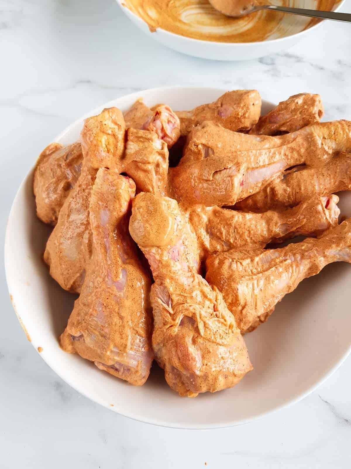 Marinated raw chicken drumsticks.