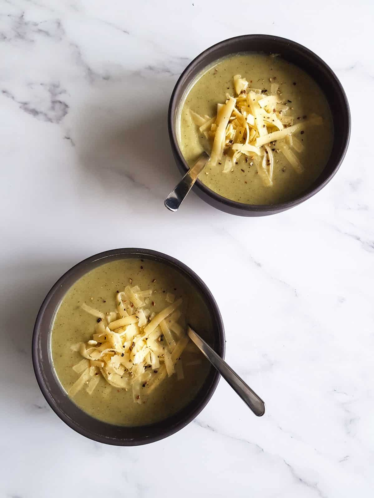 Two bowls of cauliflower broccoli soup with spoons in them.
